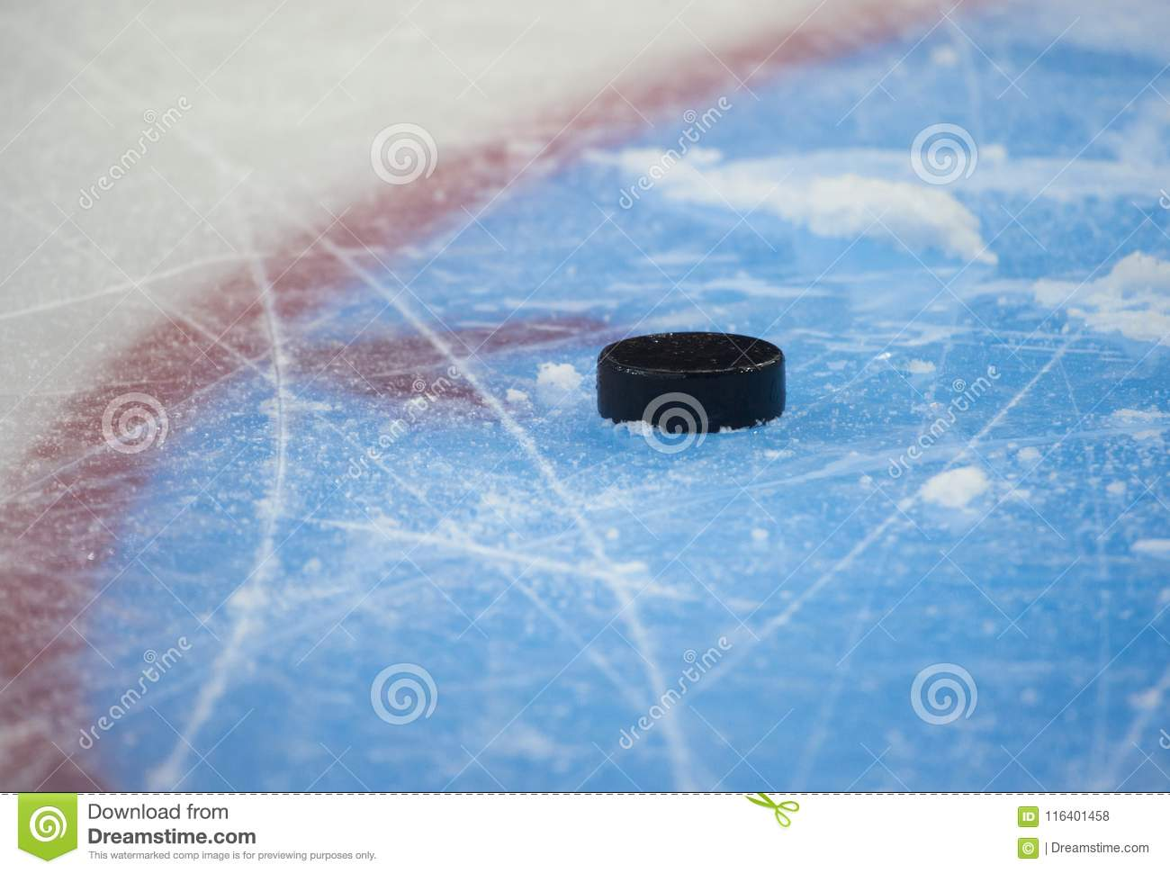 Hockey puck and stick on the ice arena