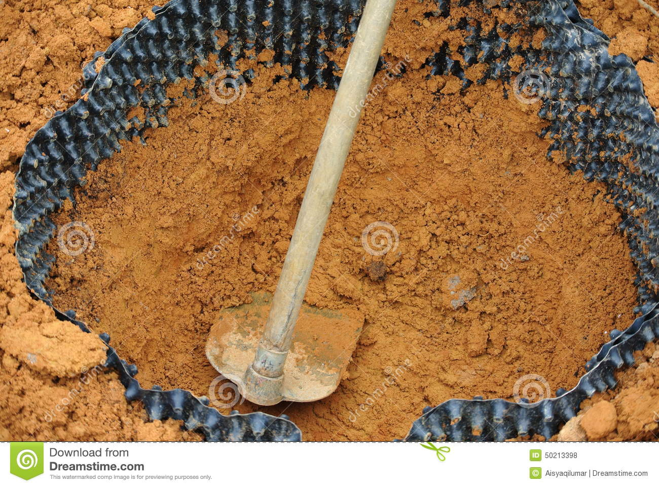 Hoe And Soil Surrounded With Plant Root Barrier Stock