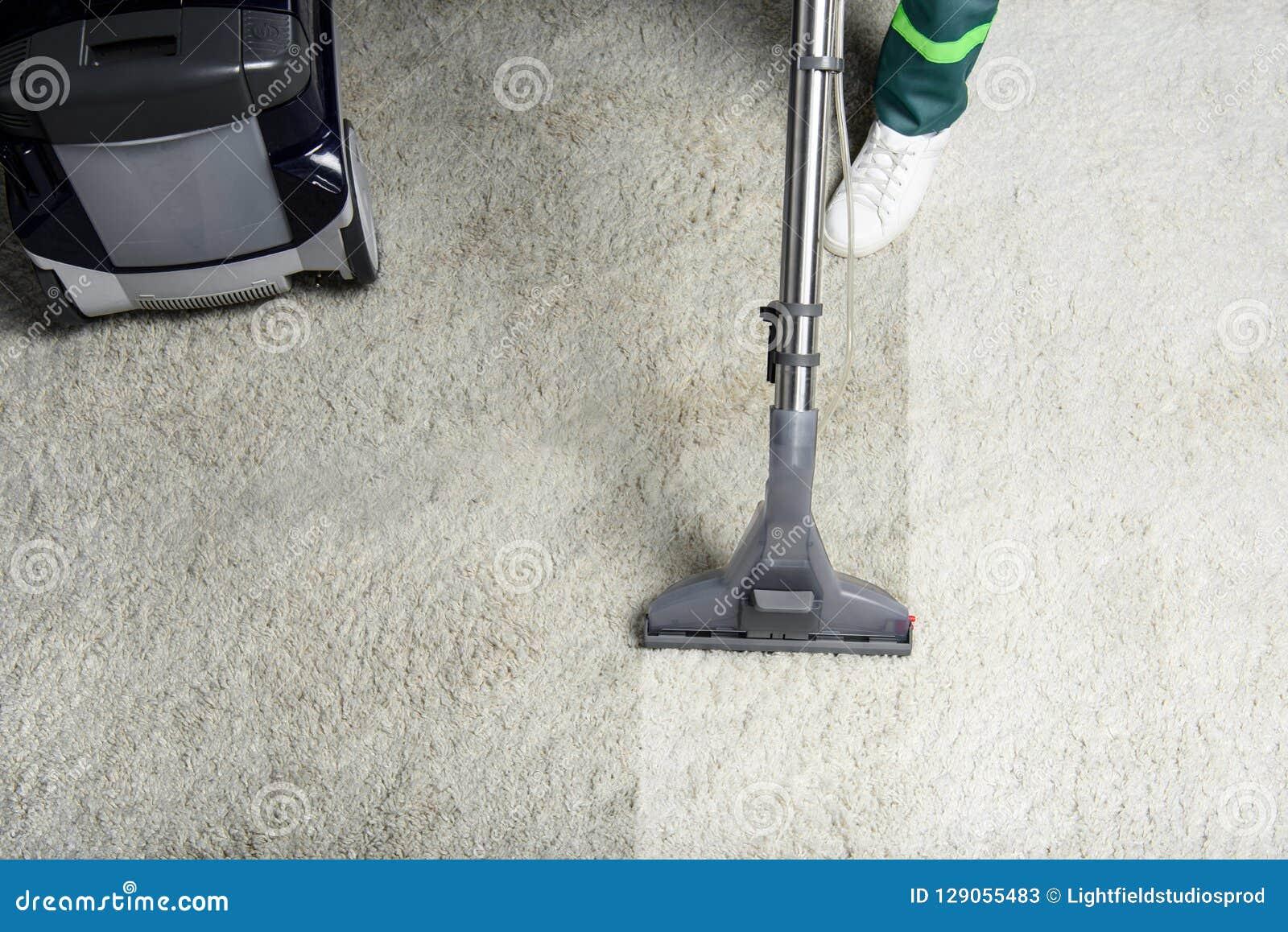 Hoge hoekmening van persoon die wit tapijt met professioneel vacuüm schoonmaken