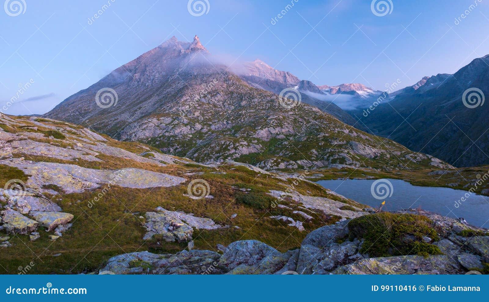 Hoge hoogte alpien meer in idyllisch land met majestueuze rotsachtige bergpieken Lange blootstelling bij schemer Brede hoekmening
