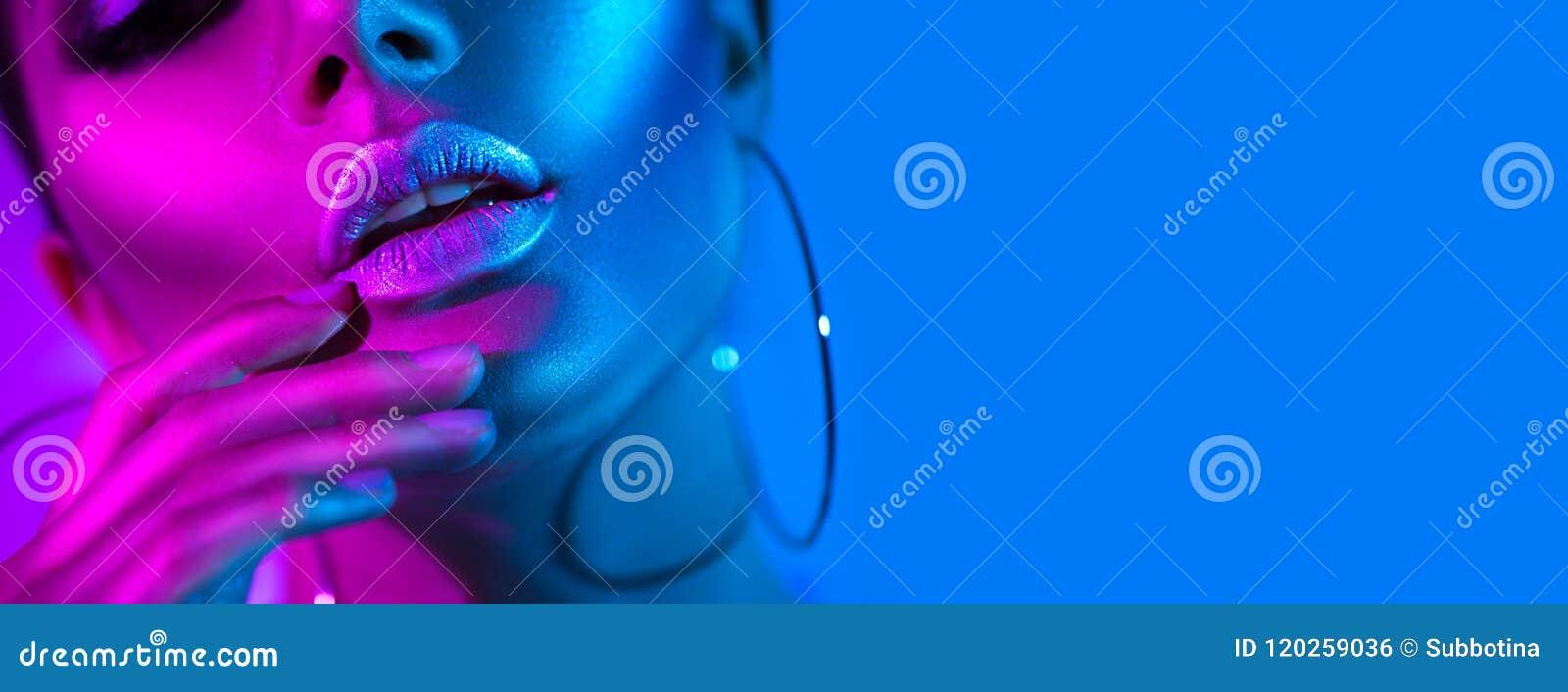 Hoge mannequinvrouw in kleurrijke heldere neonlichten die in studio stellen Mooi sexy meisje