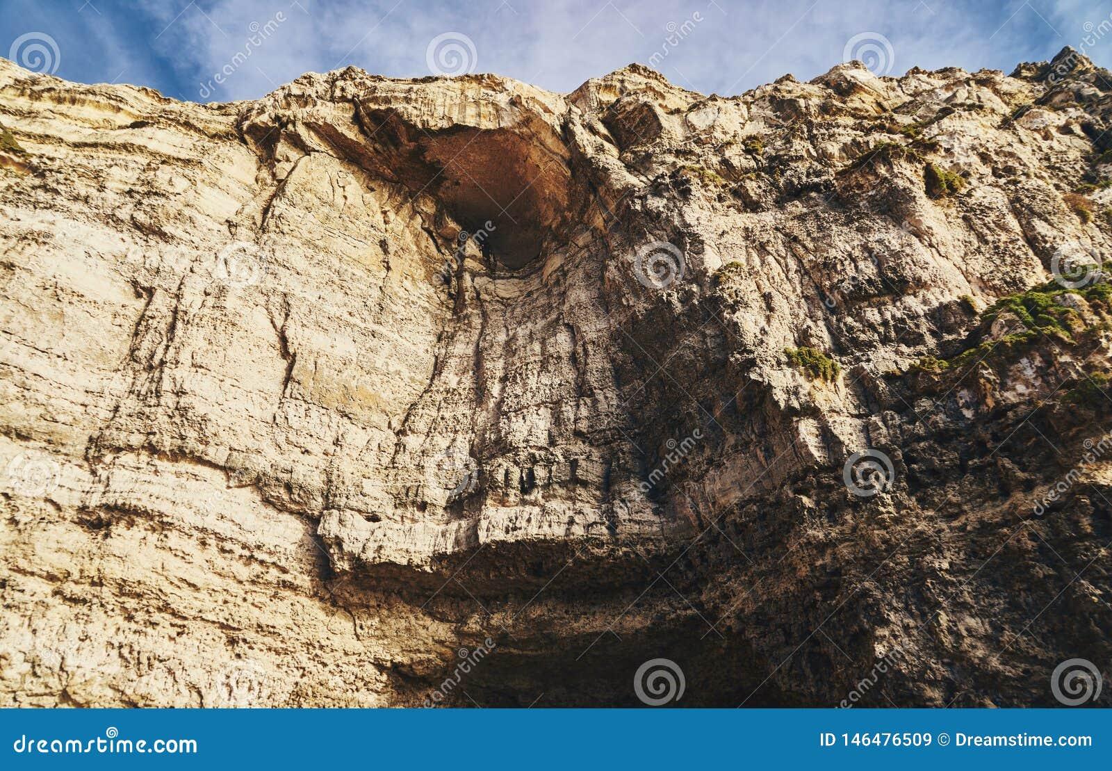 Hoge rotsmuur met hol
