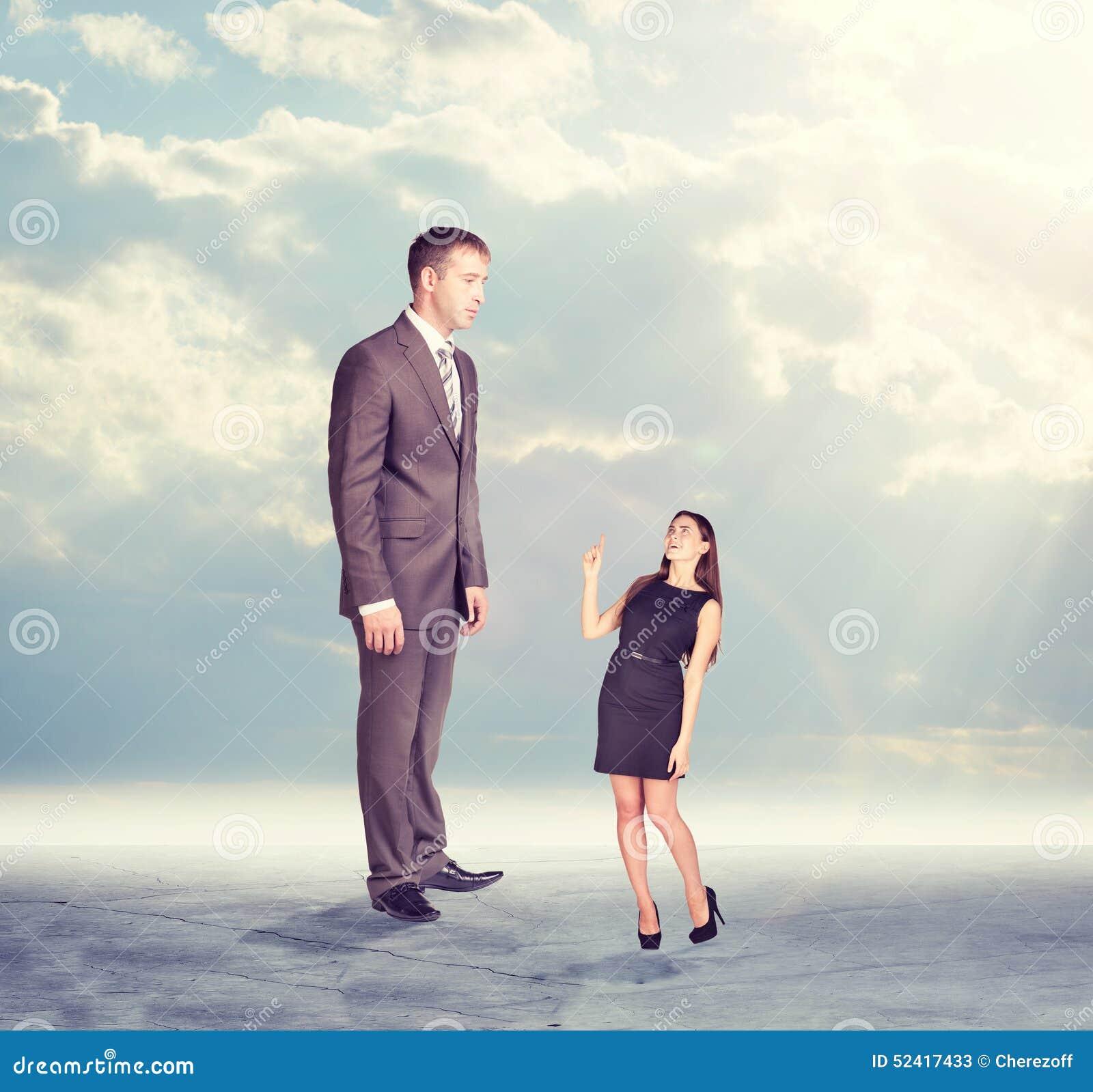 Hoge zakenman die neer weinig vrouw binnen bekijken