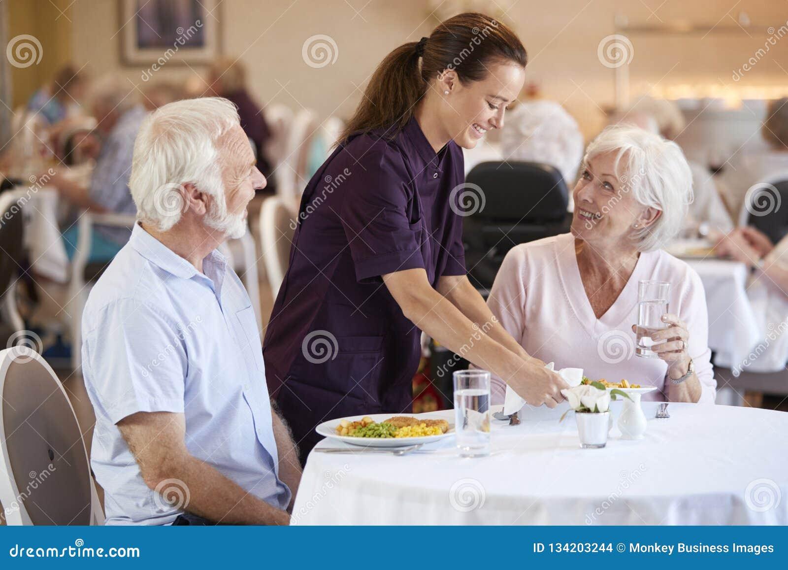 Hoger Paar die met Maaltijd door Werker uit de hulpverlening in Eetkamer van Pensioneringshuis worden gediend