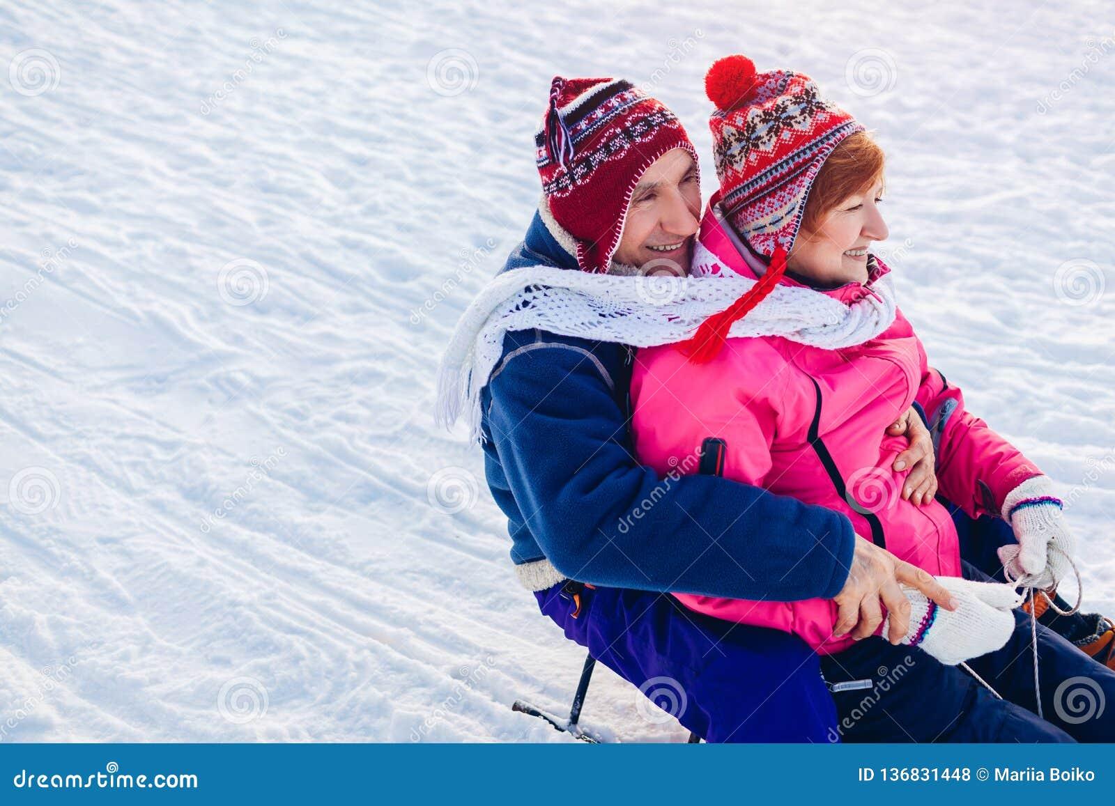 Hoger paar die neer sledding Familie die pret in de winterpark hebben De dag van de valentijnskaart `s
