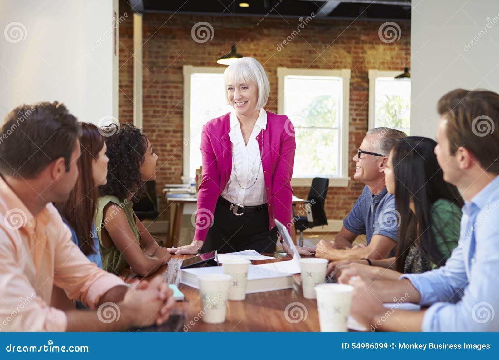 Hoger Vrouwelijk Chef- Addressing Office Workers op Vergadering