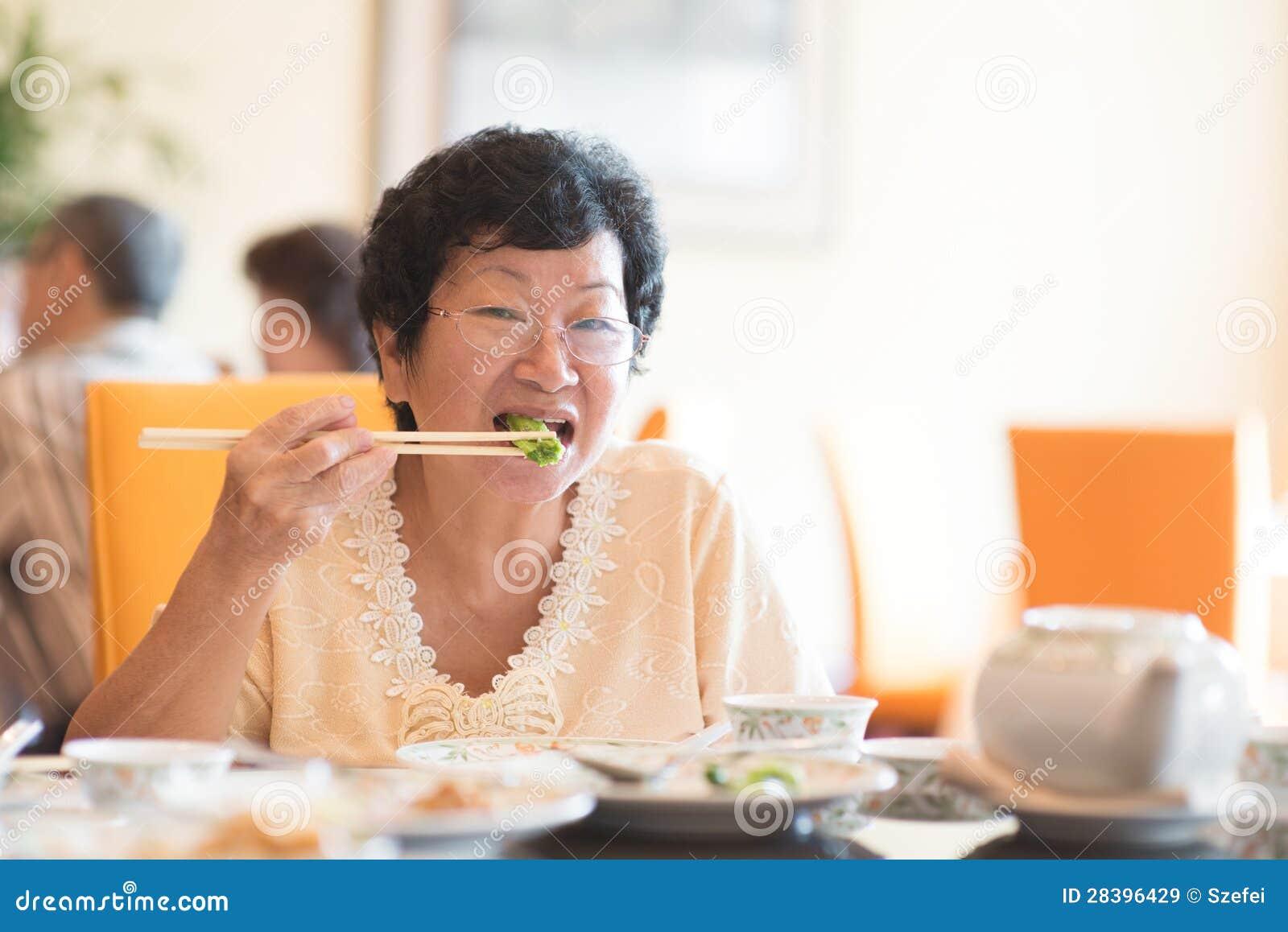 Hogere Aziatische Vrouw die groente eten
