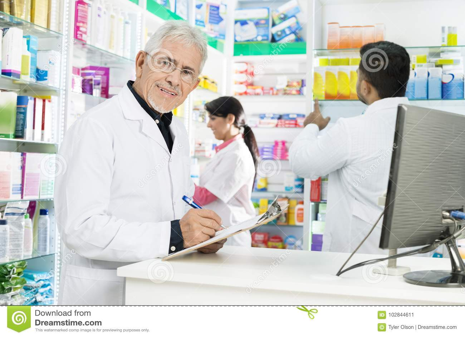 Hogere Chemicus Writing On Clipboard terwijl Medewerkers die in P werken