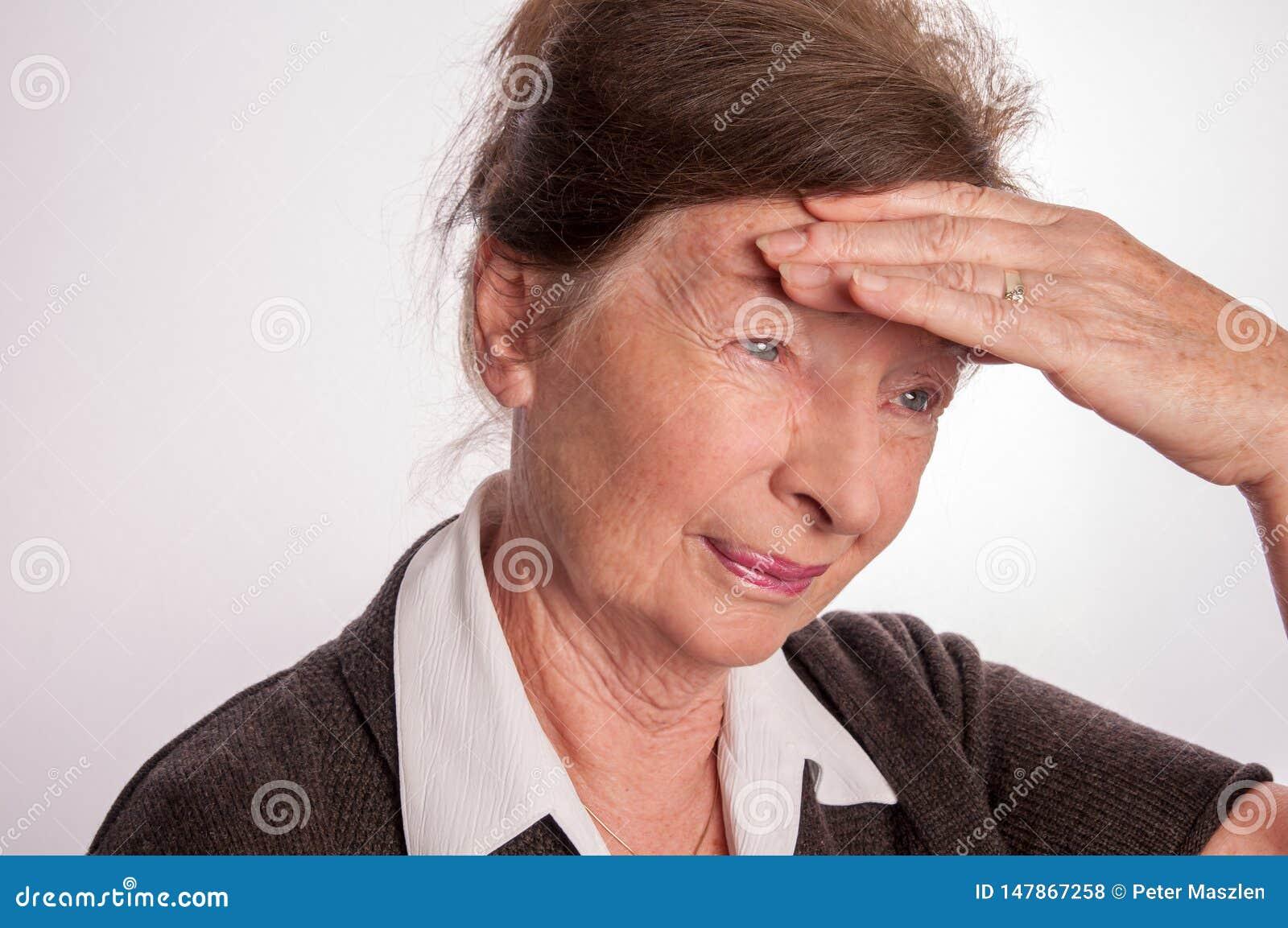 Hogere die vrouw met hoofdpijn op wit wordt geïsoleerd