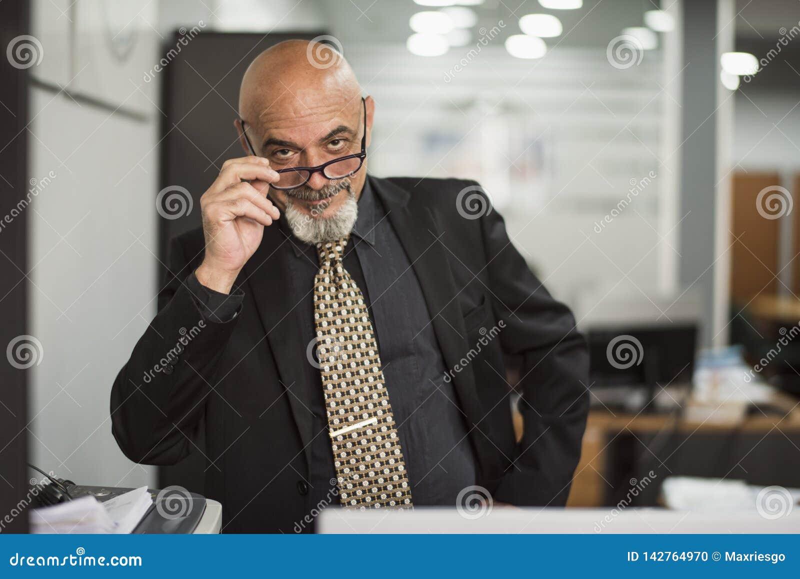 Hogere kale mens die in bureau met zwart kostuum werken