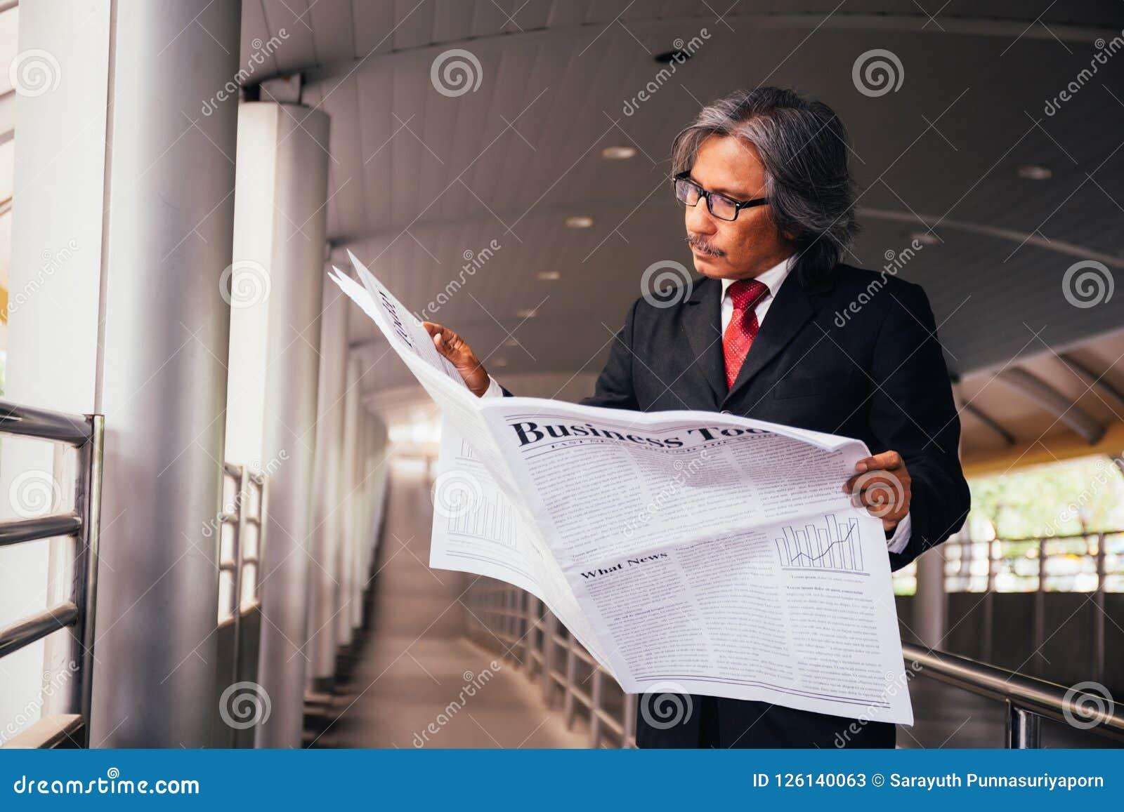 Hogere mannelijke directeur die traditionele krant buiten het bedrijf lezen