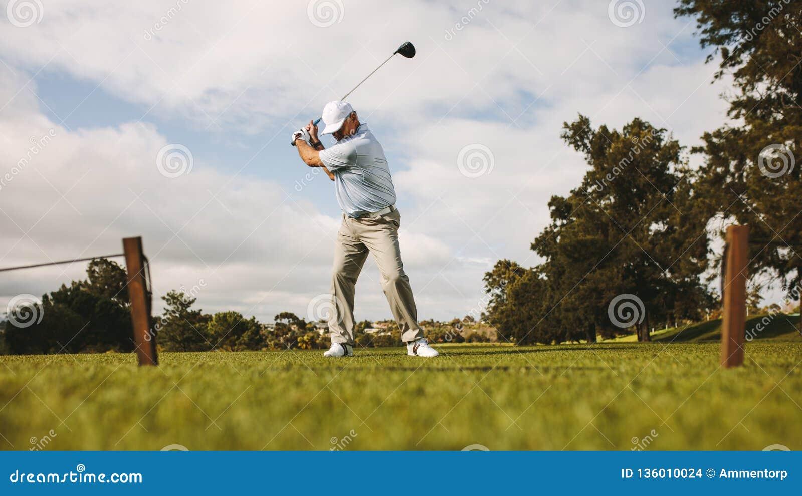 Hogere mannelijke golfspeler die schot nemen