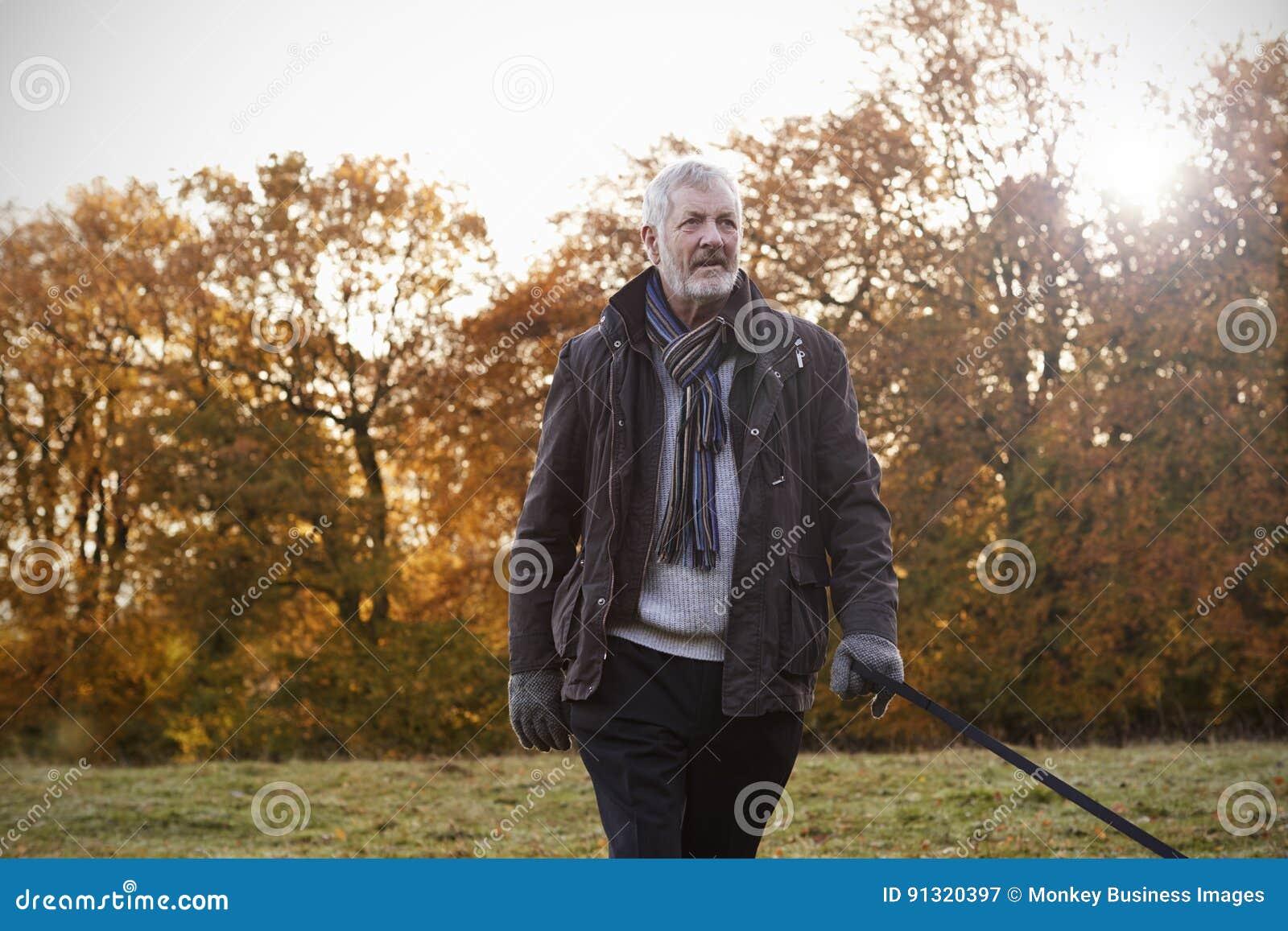 Hogere Mens die Hond voor Gang in Autumn Landscape nemen