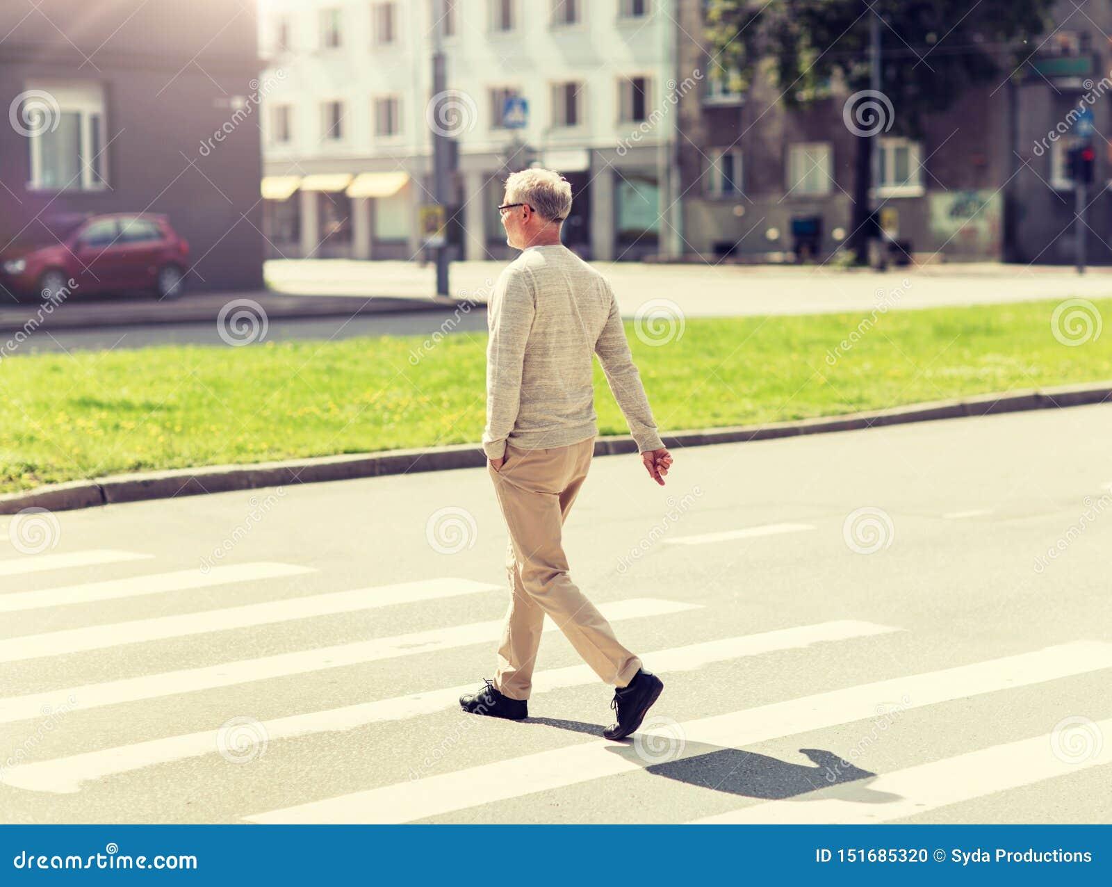 Hogere mens die langs stadszebrapad lopen