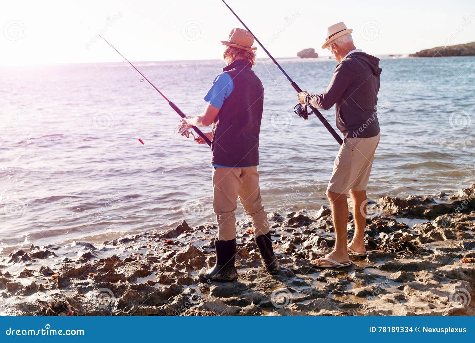 Hogere mens die met zijn kleinzoon vissen