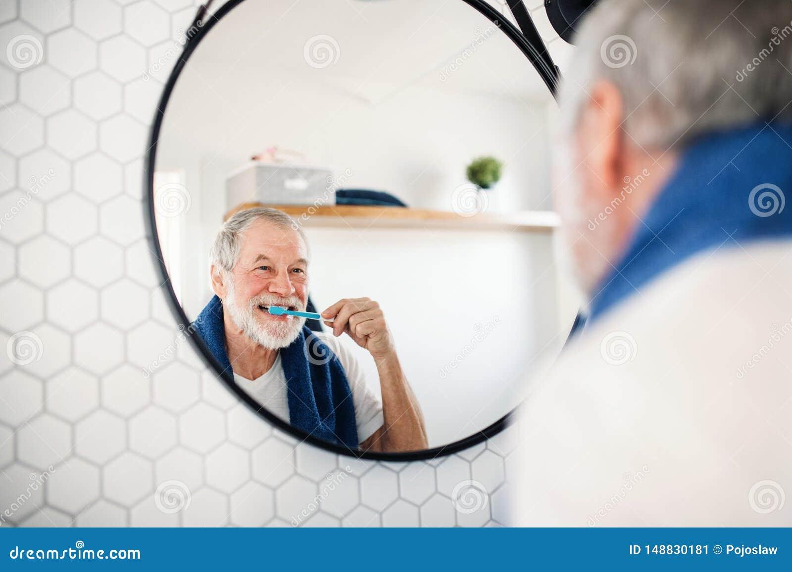 Hogere mens het borstelen tanden in badkamers binnen thuis De ruimte van het exemplaar