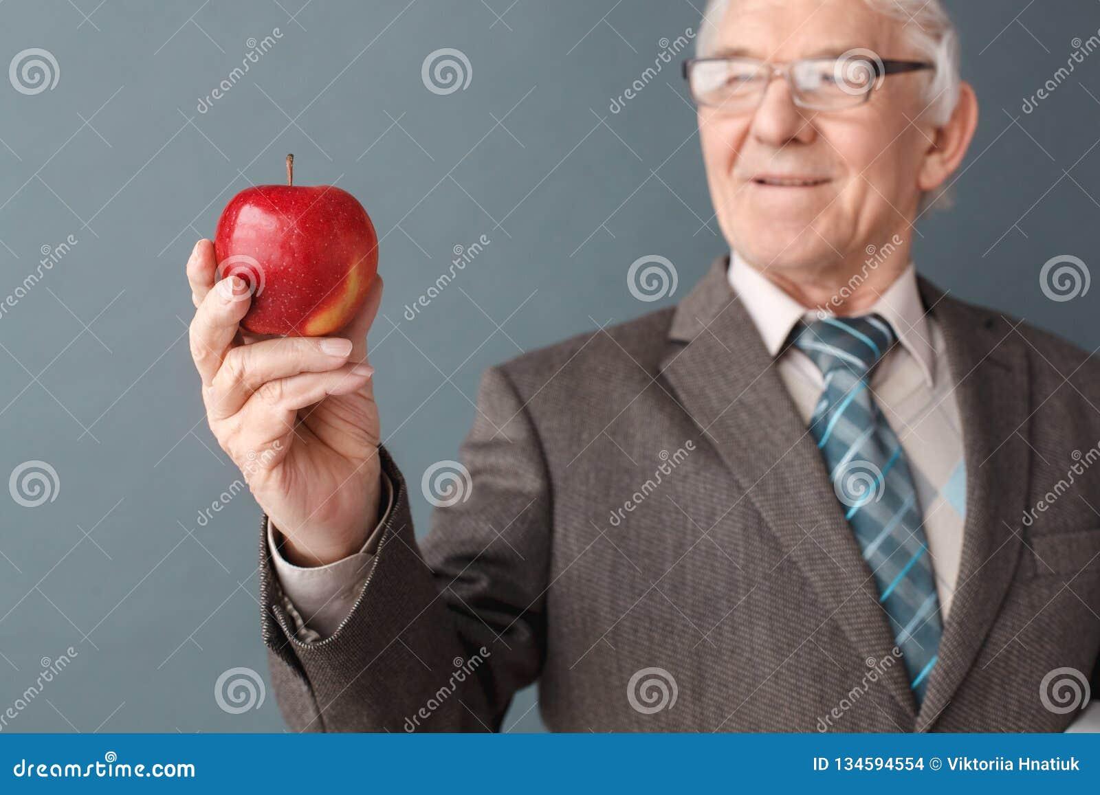 Hogere mensenleraar die glazenstudio dragen die zich bij het grijze bekijken appel bevinden die blij close-up vaag denken