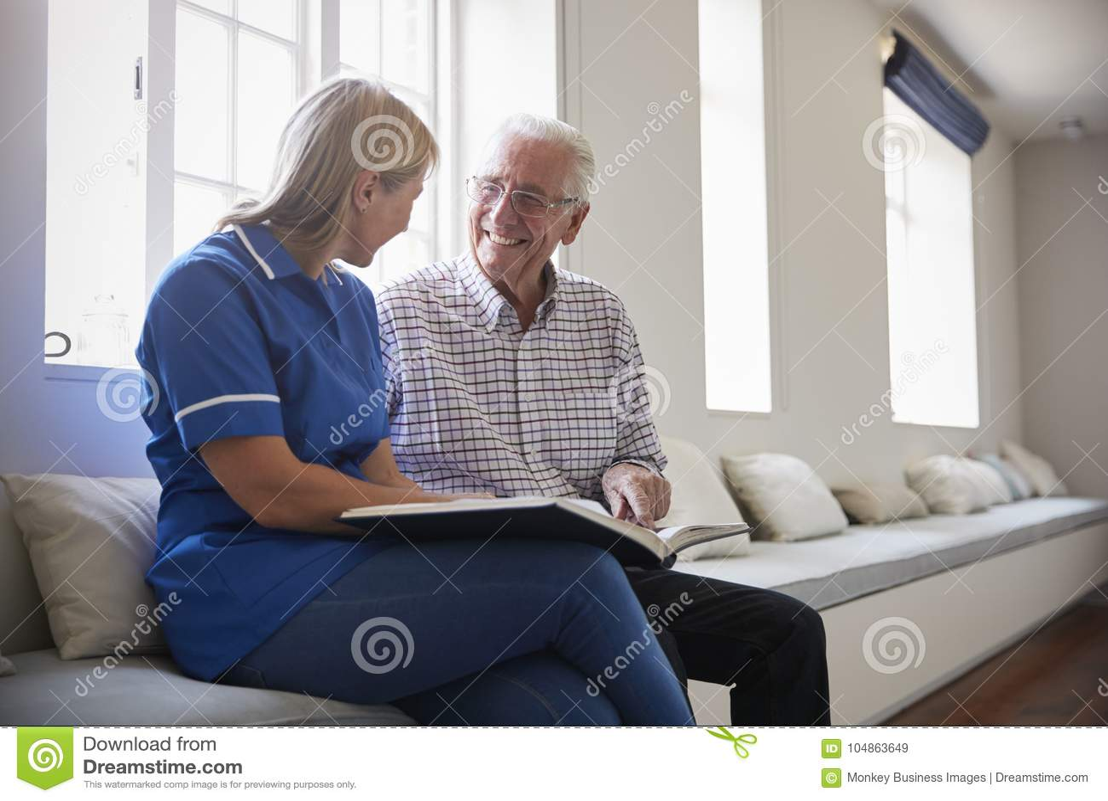 Hogere mensenzitting die fotoalbum bekijken met zorgverpleegster