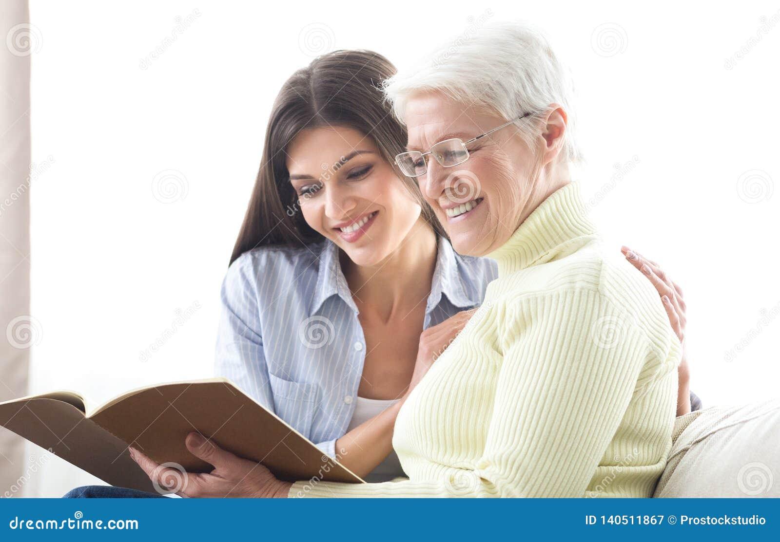Hogere moeder en dochter die catalogus, die nieuw huis zoeken kijken