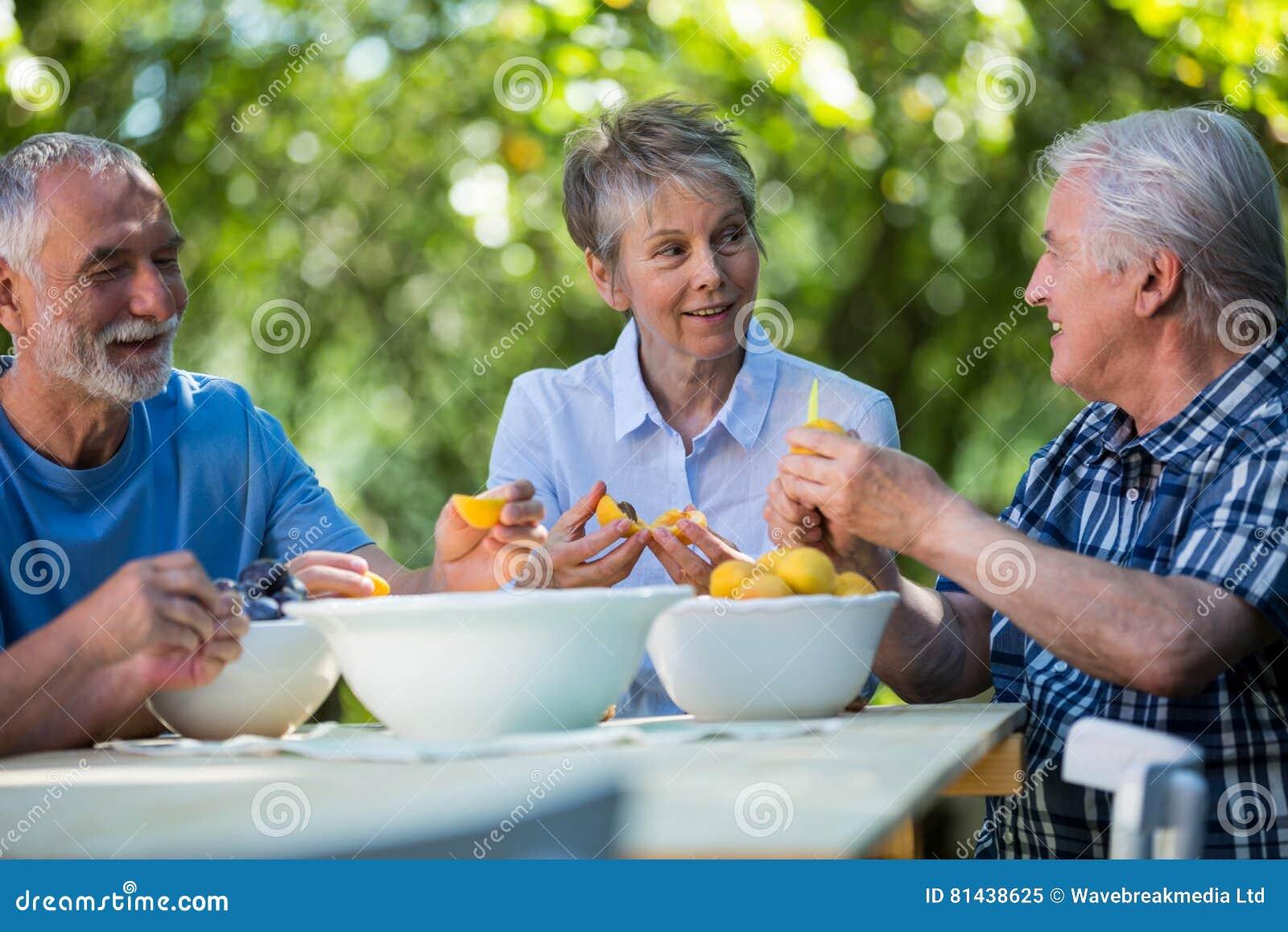 Hogere paren die zaden van abrikozenvruchten verwijderen in tuin