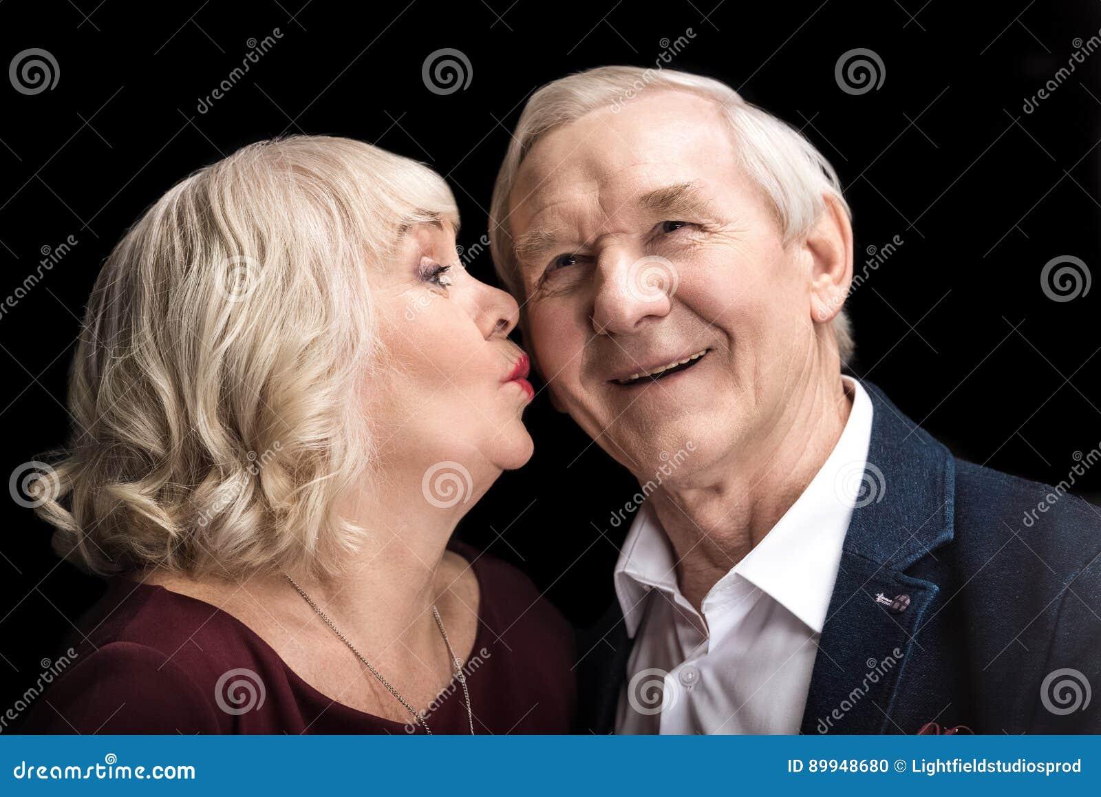 Hogere vrouw die de gelukkige mens op zwarte kussen