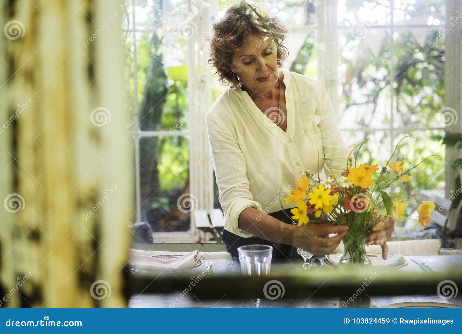 Hogere vrouw die verse bloemen schikken