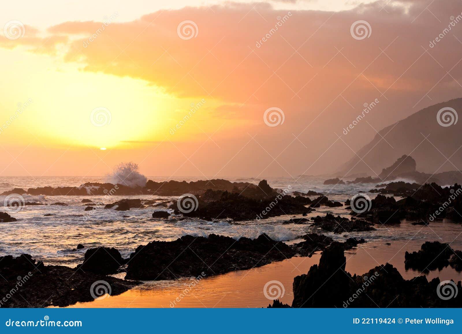 Hohe Welle, die auf den Felsen bricht