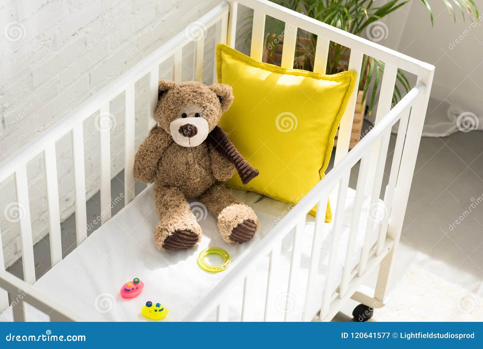 Hohe Winkelsicht des Teddybären, anderer Spielwaren und des gelben Kissens in der Babykrippe
