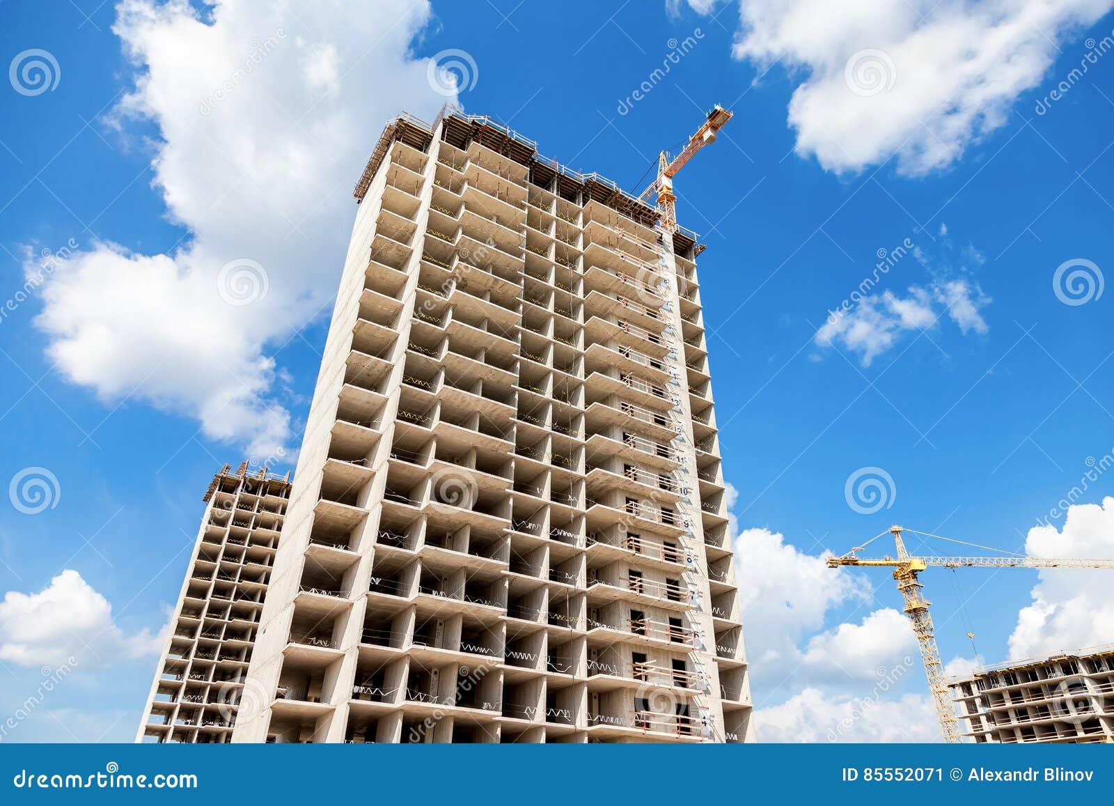 Hohe Wohngebäude im Bau mit Kränen gegen