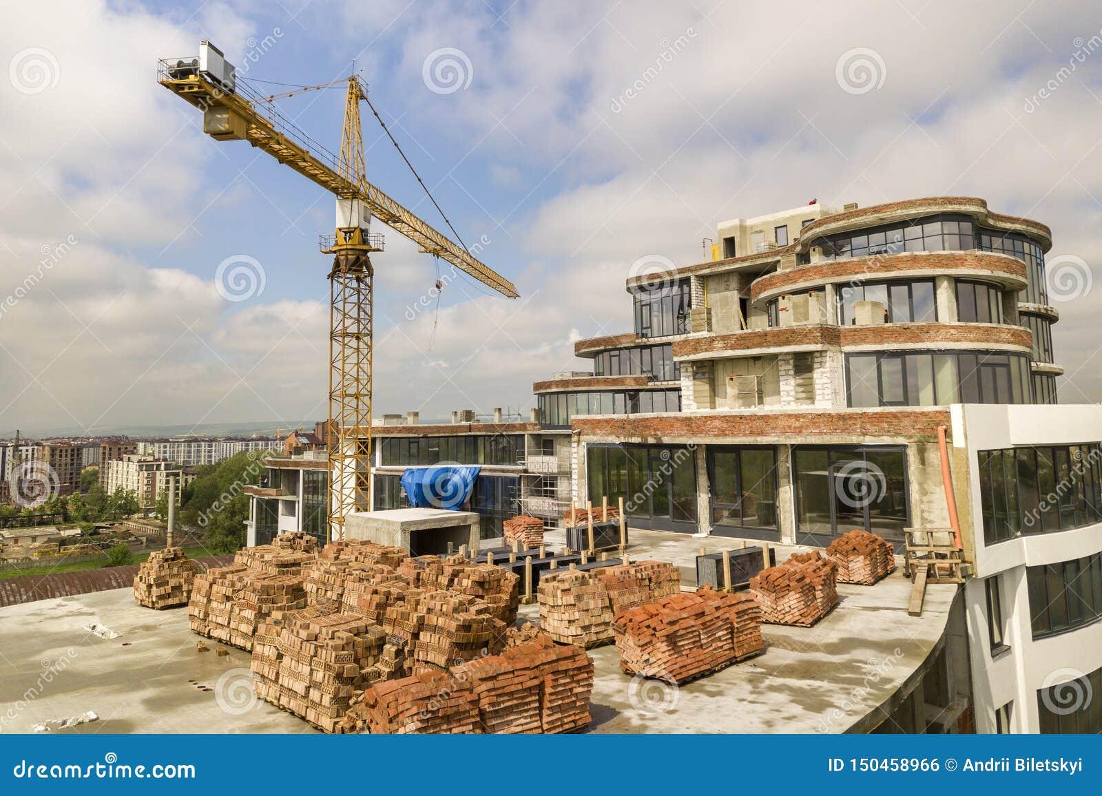 Hohes Gebäude der Wohnung oder des Büros im Bau Backsteinmauern, Glasfenster, Baugerüst und konkrete Stützsäulen Turm