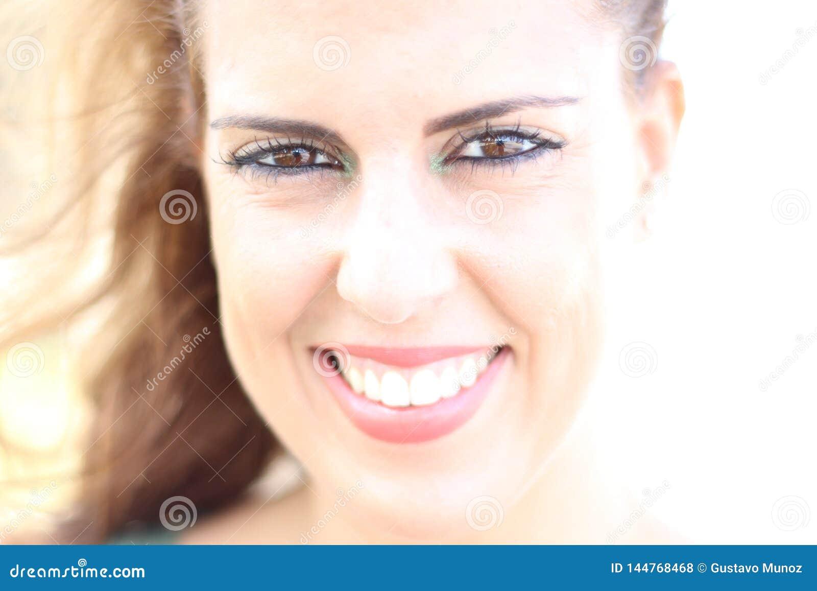 Hohes Schlüsselporträt der brunette jungen Frau, die an einem sonnigen Tag lächelt