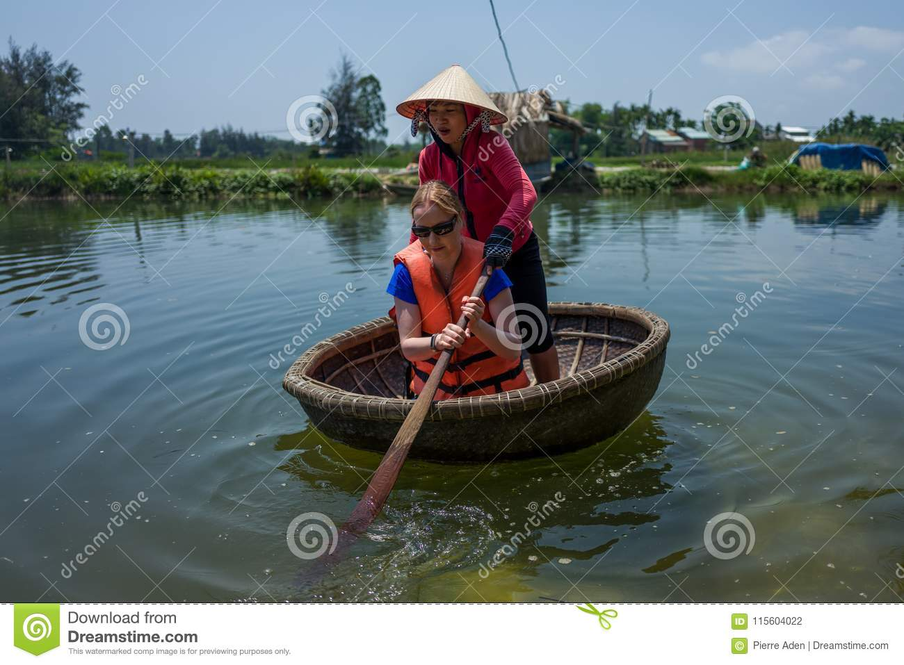 Hoi An, Vietnam - April 21, 2018: Caucasian woman learns to use Thung Chai round boat with guide in Hoi An.