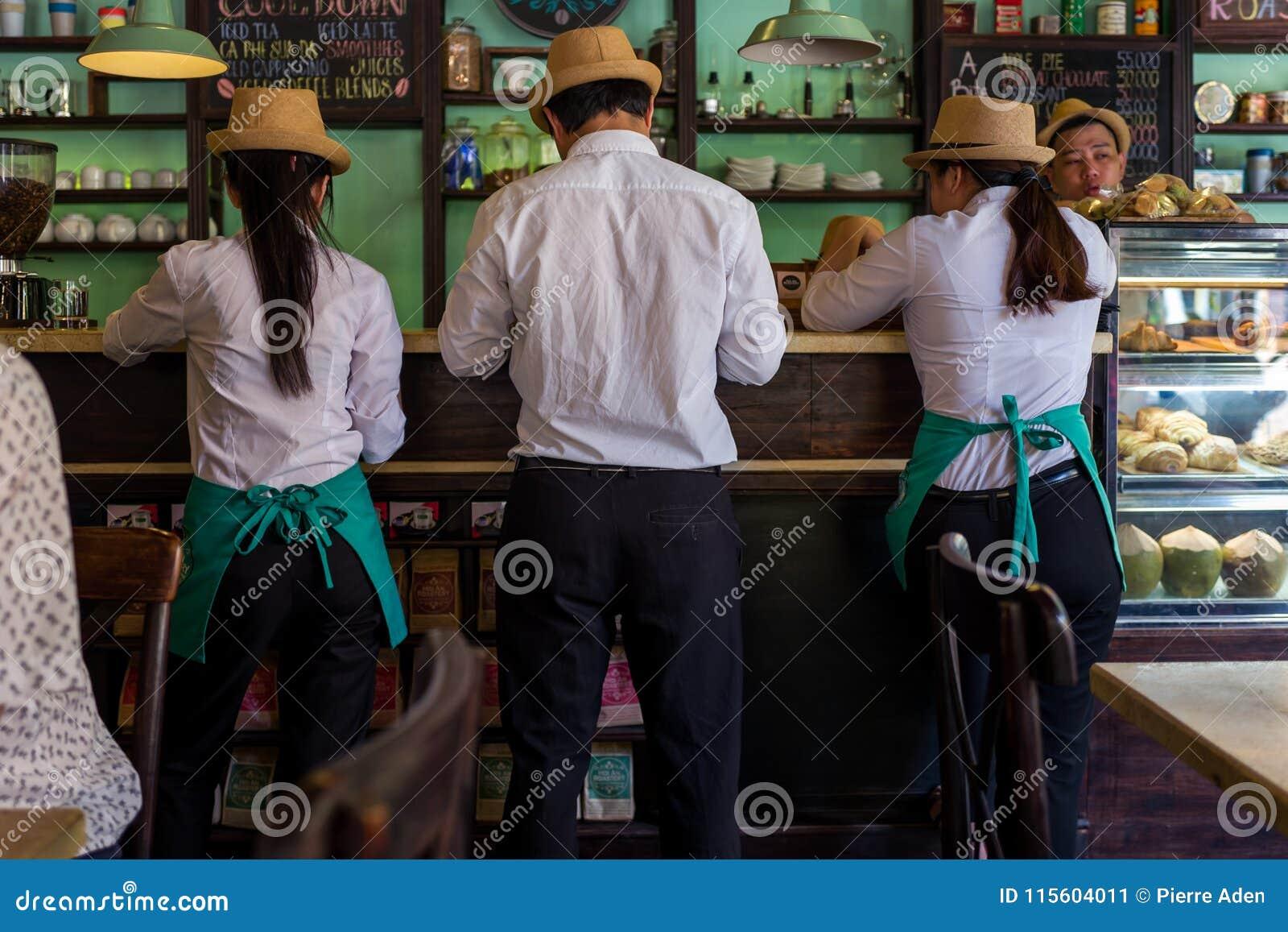 Hoi An, Vietnam - April 20, 2018: De kelner en de serveersters controleren een orde bij een bar in Hoi An