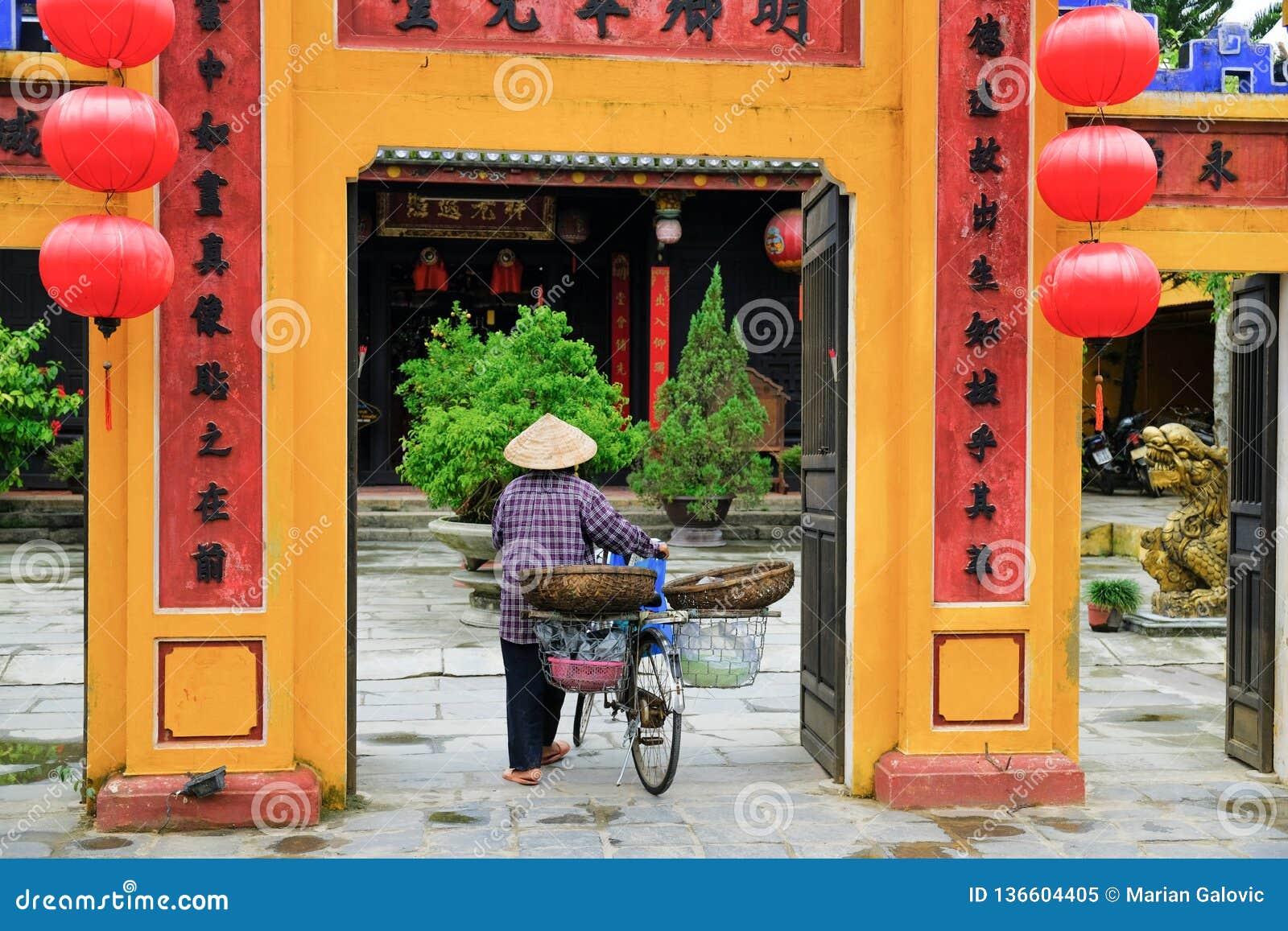 Hoi An/Vietnam, 11/11/2017 : Femme vietnamienne locale avec le chapeau et la bicyclette de riz entrant dans une salle de réunion