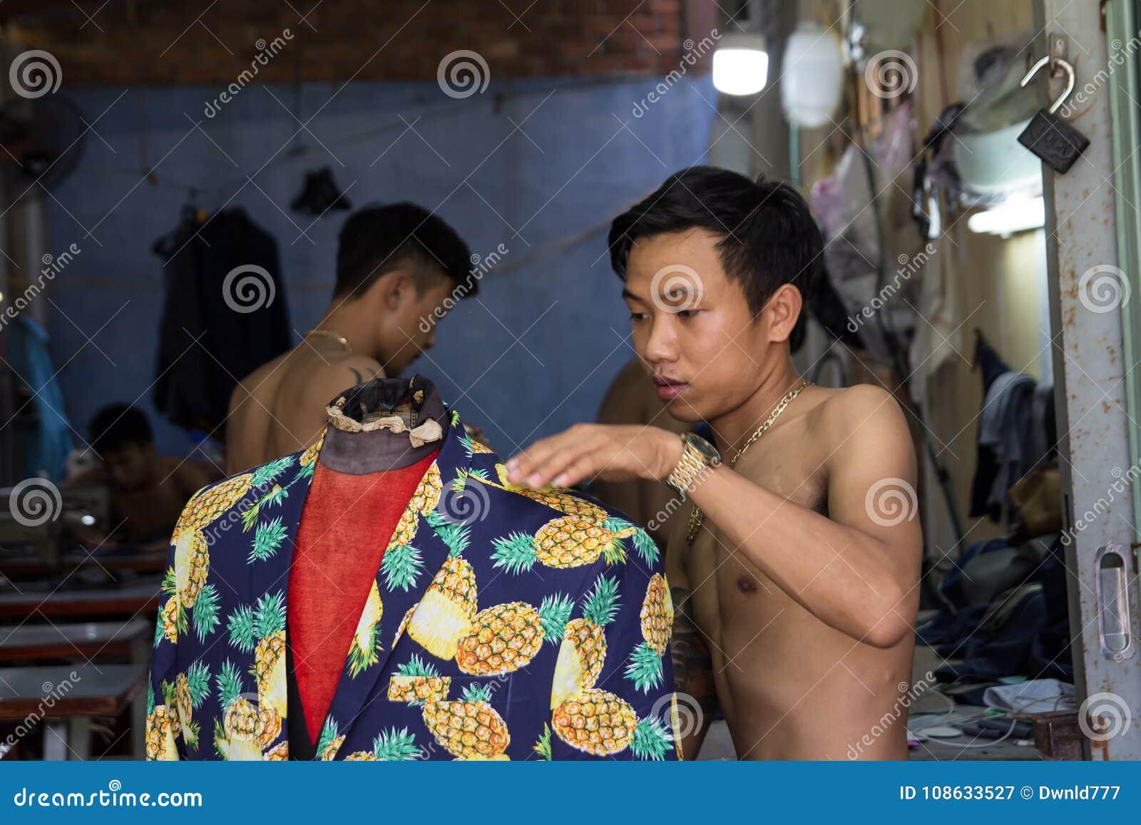 Adatti l uomo che fa i vestiti nell officina del tessuto nel Vietnam 85a6e3e220d