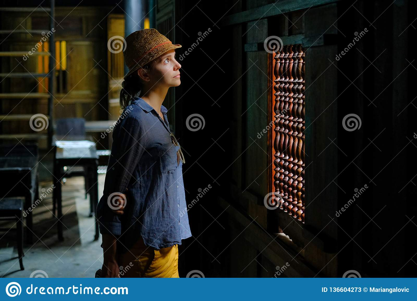 Hoi An/Vietnam, 11/11/2017: Weibliche touristische Stellung im dunklen hölzernen Innenraum eines traditionellen Hauses Tan Ky in
