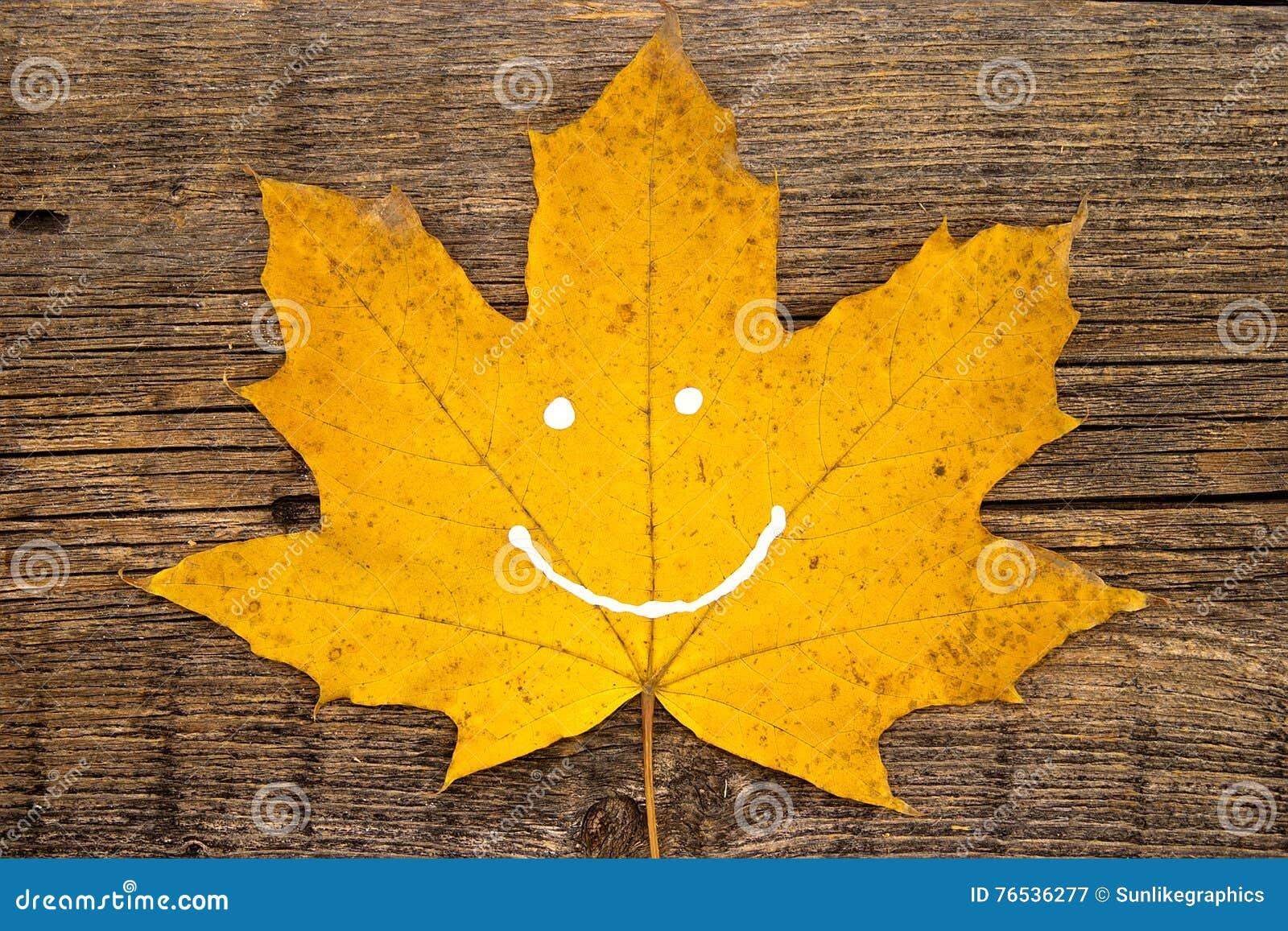 Hoja amarilla del otoño con sonrisa en fondo de madera rústico autum