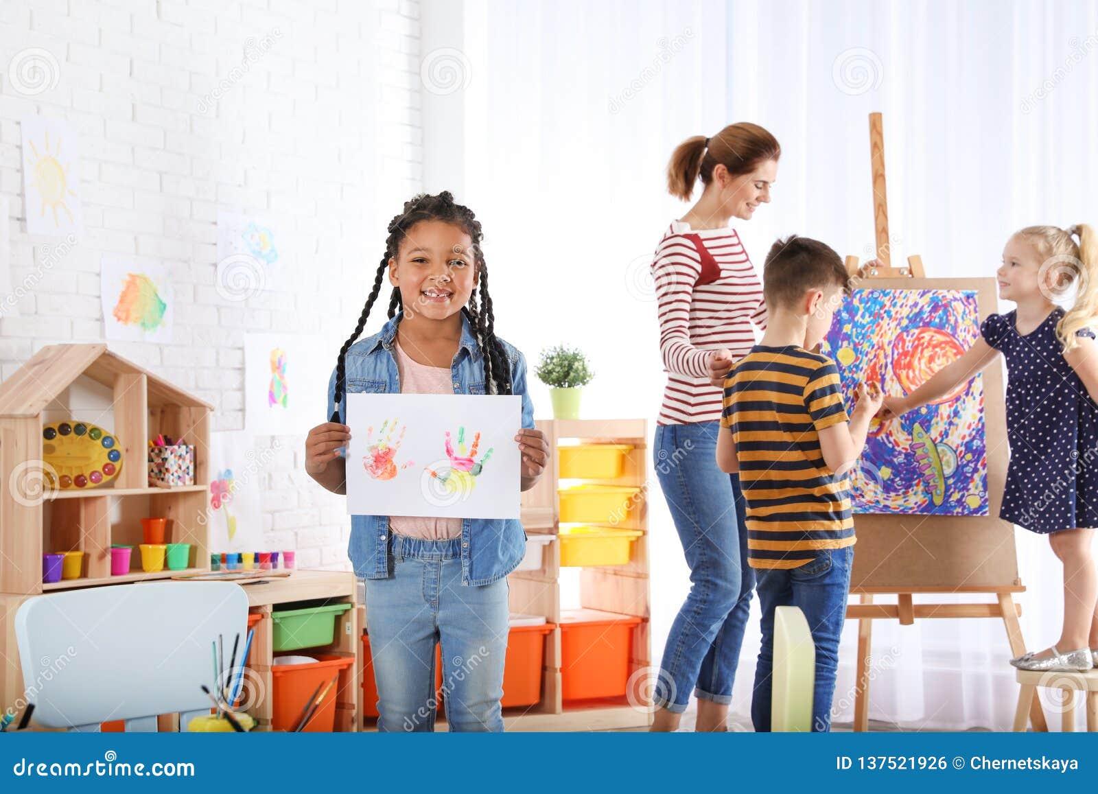 Hoja de papel linda de la demostración del pequeño niño con las impresiones coloridas de la mano dentro