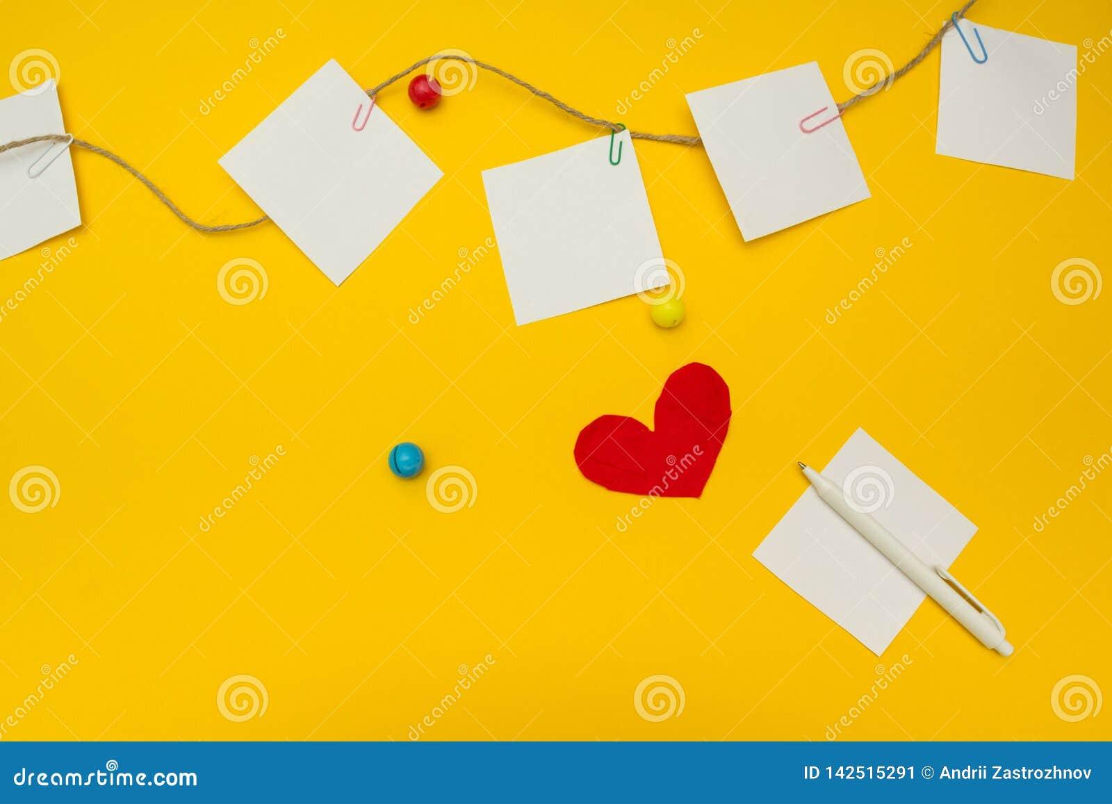 Hoja de papel vacía en un fondo amarillo Documento de nota sobre la cuerda La tarjeta del día de San Valentín envía el mensaje de
