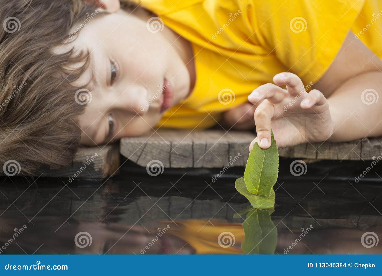 Hoja-nave verde en mano de los niños en el agua, muchacho en juego del parque con