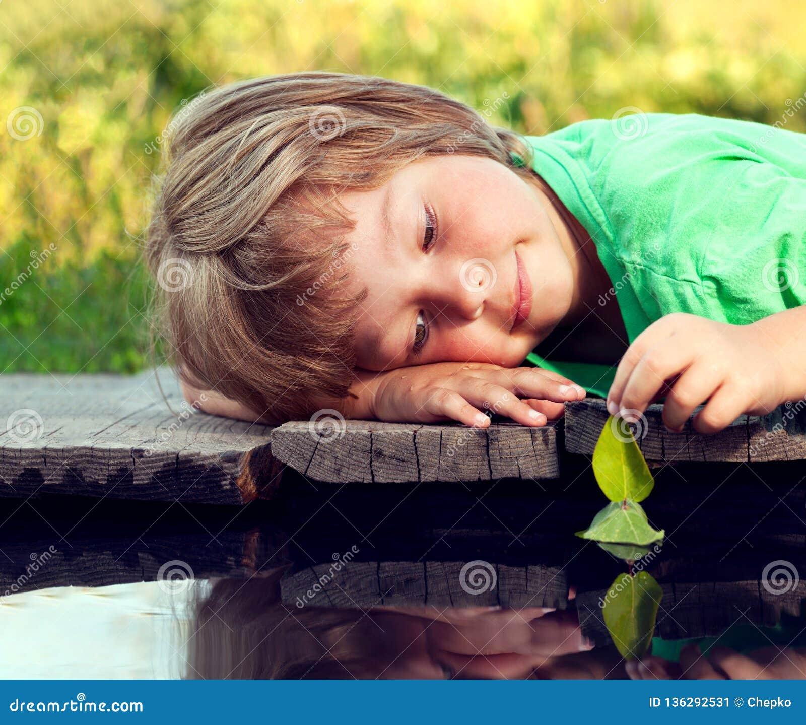 Hoja-nave verde en mano de los niños en el agua, muchacho en juego del parque con el barco en el río
