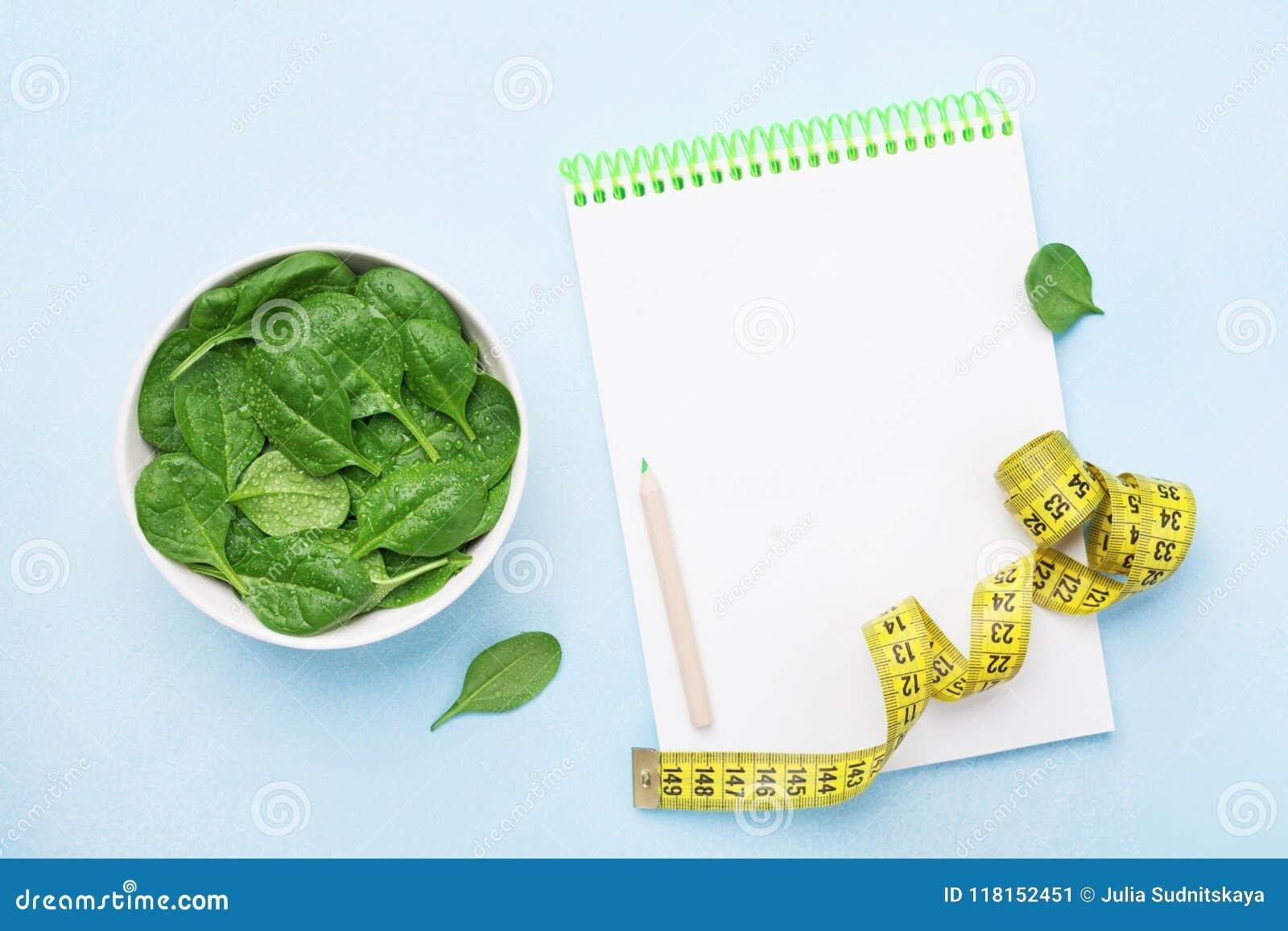 Hojas de la espinaca, cuaderno y cinta métrica verdes en la opinión de sobremesa azul Dieta y concepto sano de la comida
