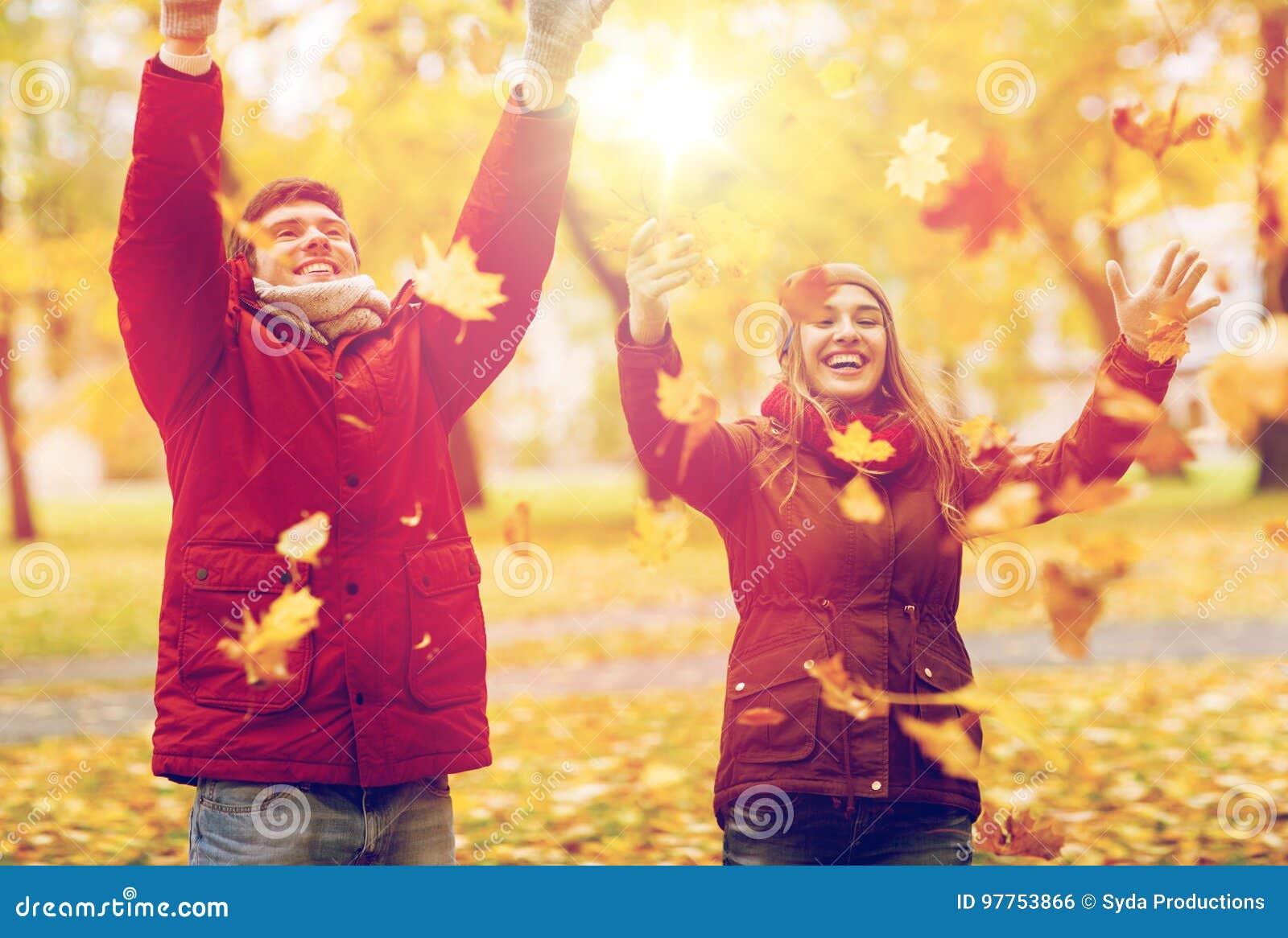Hojas de otoño de los pares que lanzan jovenes felices en parque