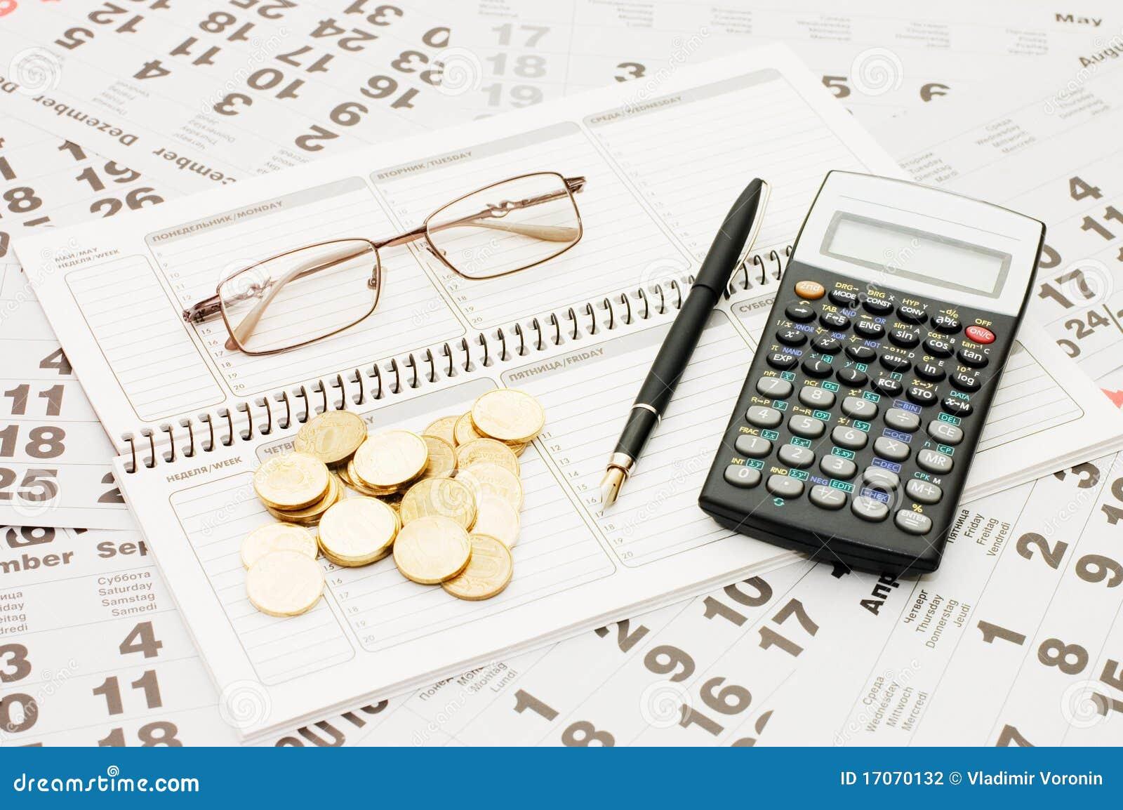 Hojas de un calendario con monedas y un cuaderno