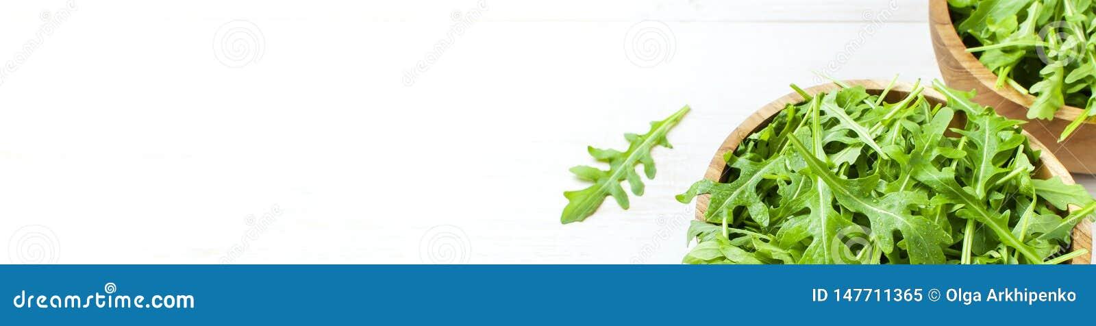 Hojas verdes frescas del arugula en el cuenco de madera, ensalada del rucola en el fondo r?stico de madera blanco con el lugar pa