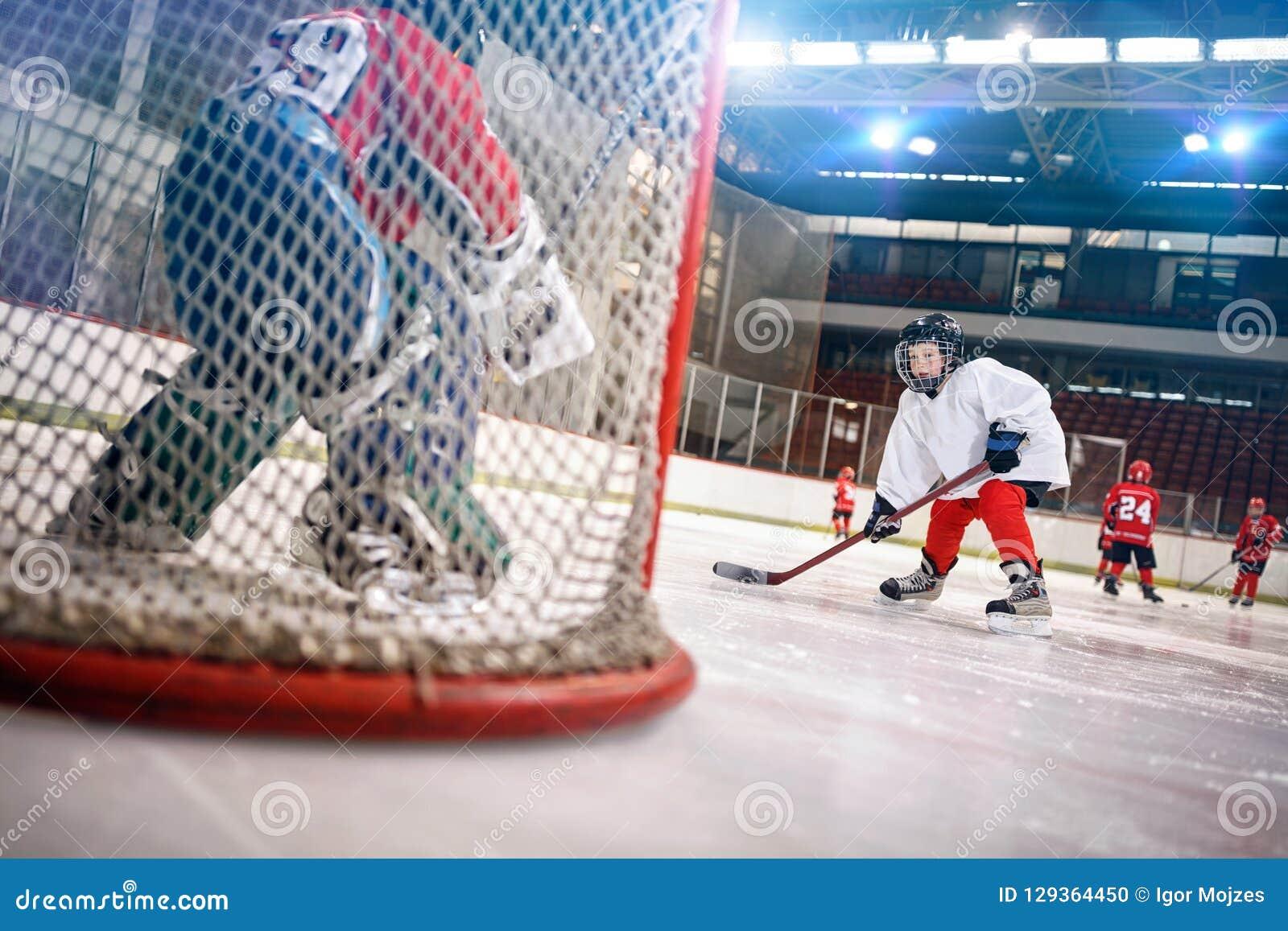Hokeja na lodzie gracz strzela krążek hokojowego na celu