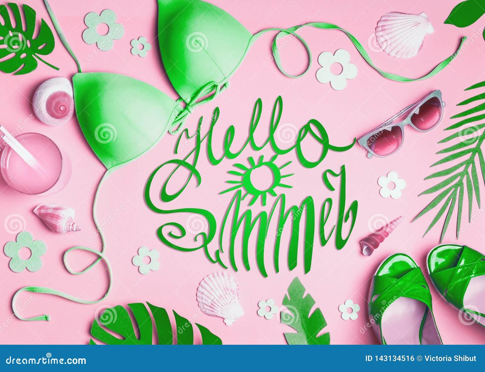 Hola verano Accesorios femeninos de la playa en el fondo rosado, visión superior Bikini verde puesto plano, gafas de sol, sandali