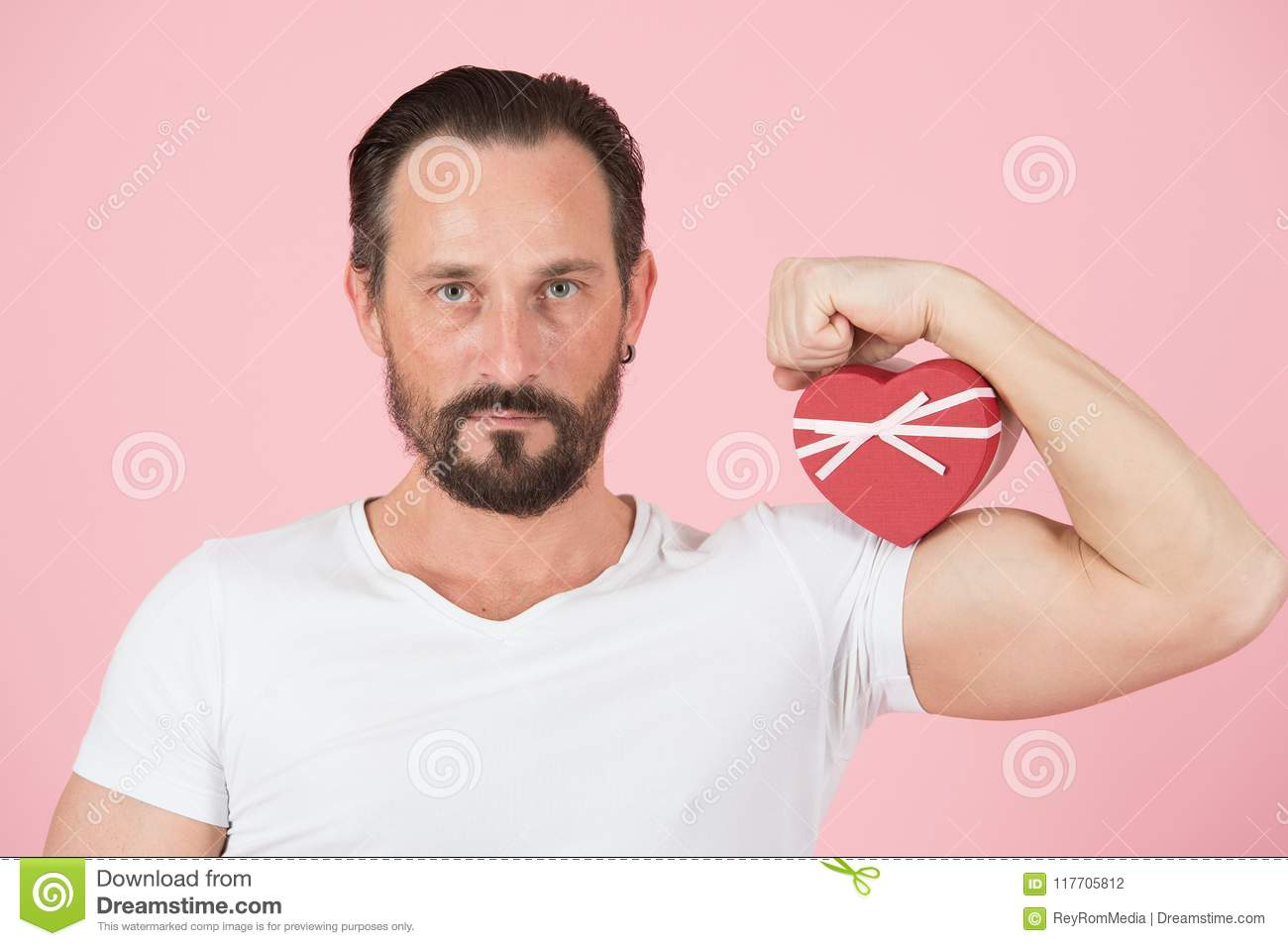 Holding Heart Against A Bicep Muscle For Valentines Day Man And