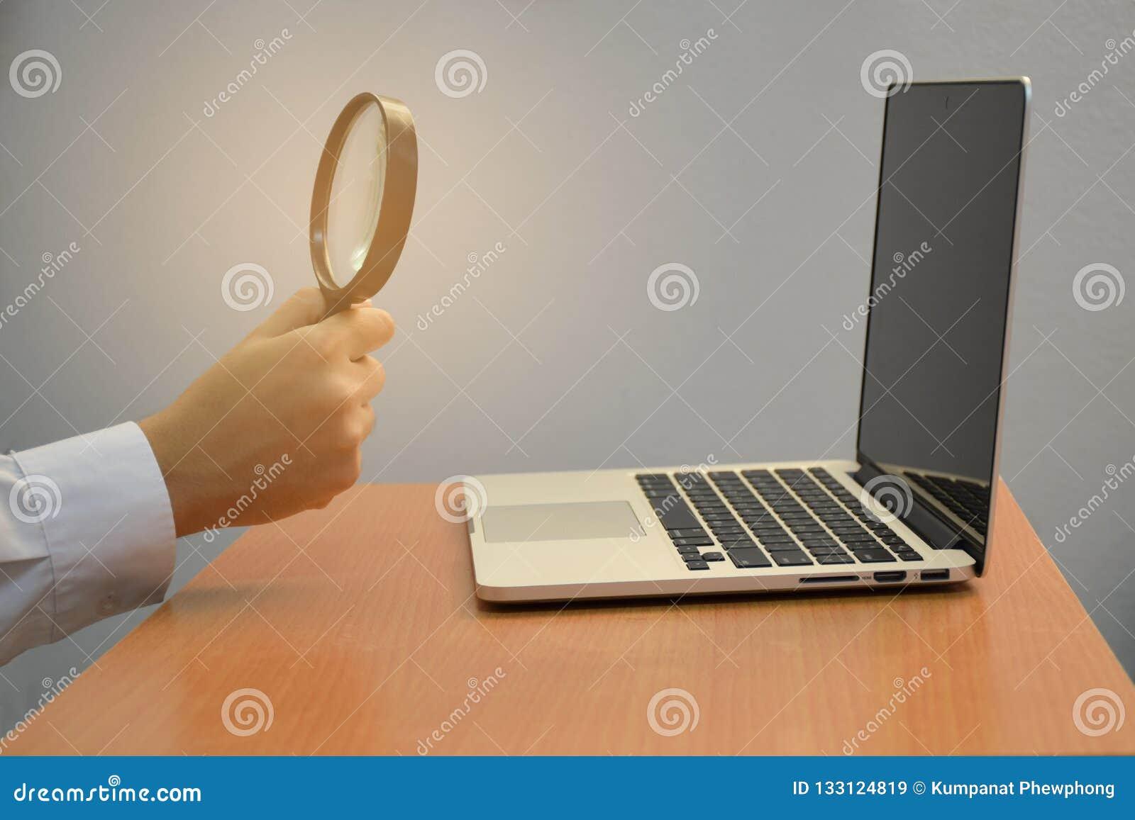 Holding-Lupensuche des Geschäfts männliche Handund Laptop oder Computer für kreatives Konzept der Idee