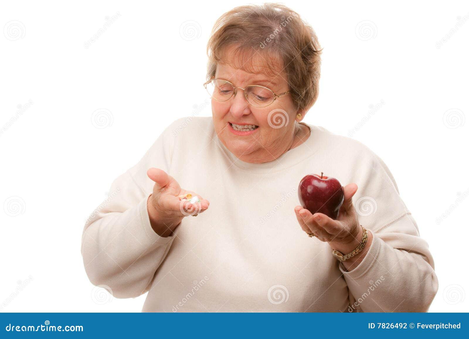 Holding maggiore confusa Apple della donna e vitamine